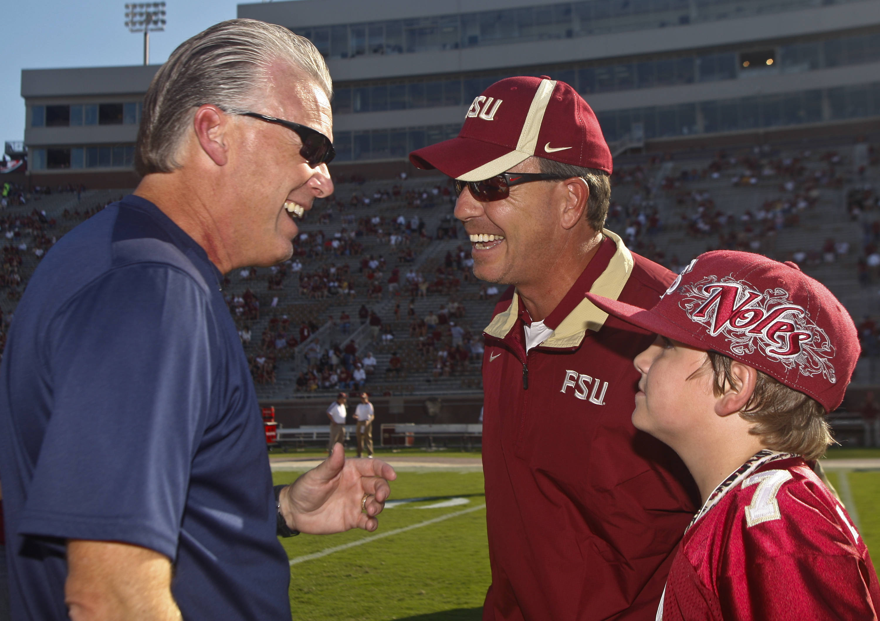 Charleston Southern head coach Jay Mills, left, shares a laugh with Florida State head coach Jimbo Fisher, center, and Fisher's son Trey Fisher, 10, prior to the start of an NCAA college football game on Saturday, Sept. 10, 2011, in Tallahassee, Fla. (AP Photo/Phil Sears)