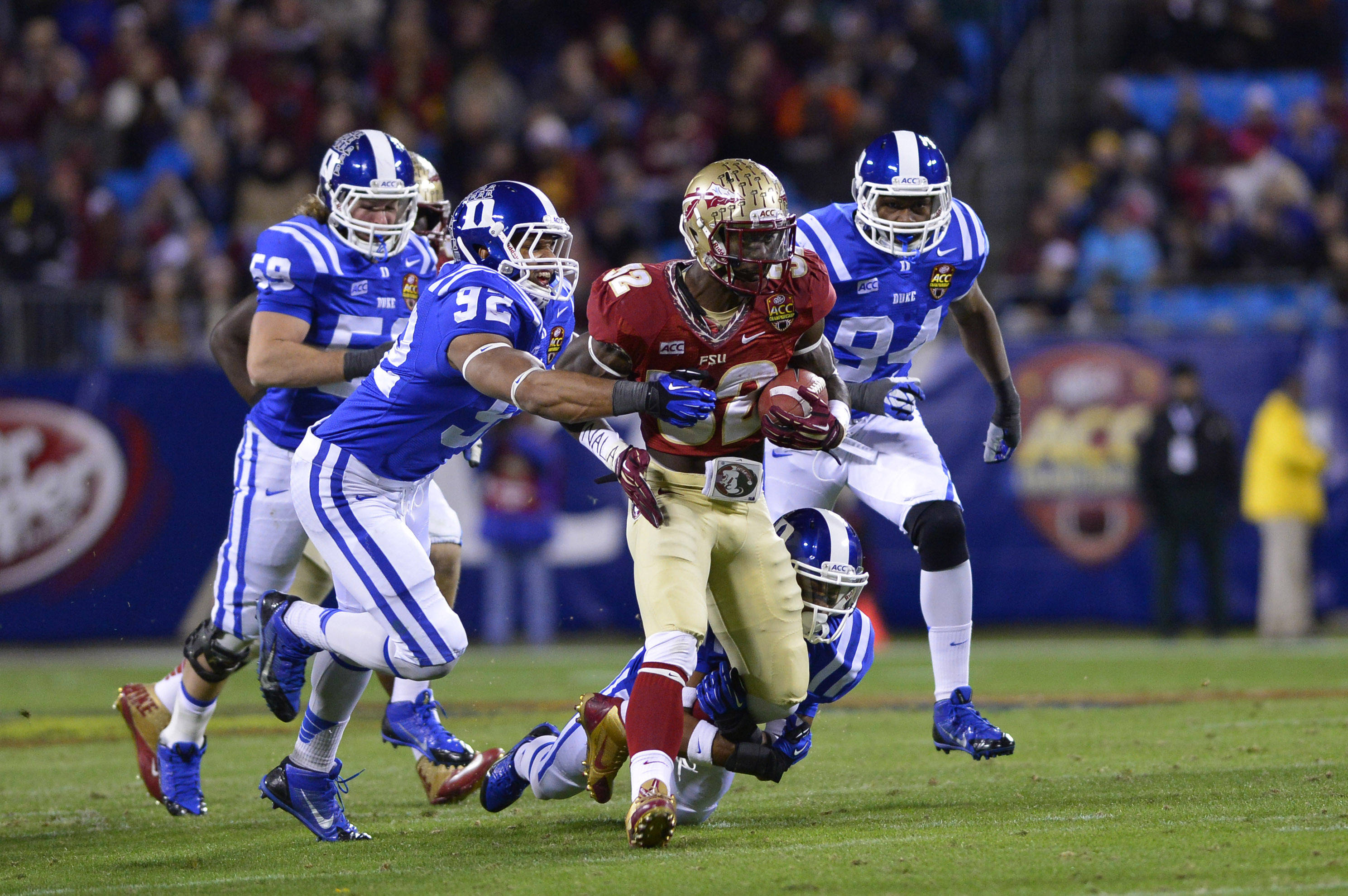 Dec 7, 2013; Charlotte, NC, USA; Florida State Seminoles running back James Wilder Jr. (32) runs as Duke Blue Devils linebacker Kelby Brown (59) and defensive end Justin Foxx (92) and cornerback Deondre Singleton (33) and defensive end Jordan DeWalt-Ondijo (94) defend in the first quarter at Bank of America Stadium. Mandatory Credit: Bob Donnan-USA TODAY Sports