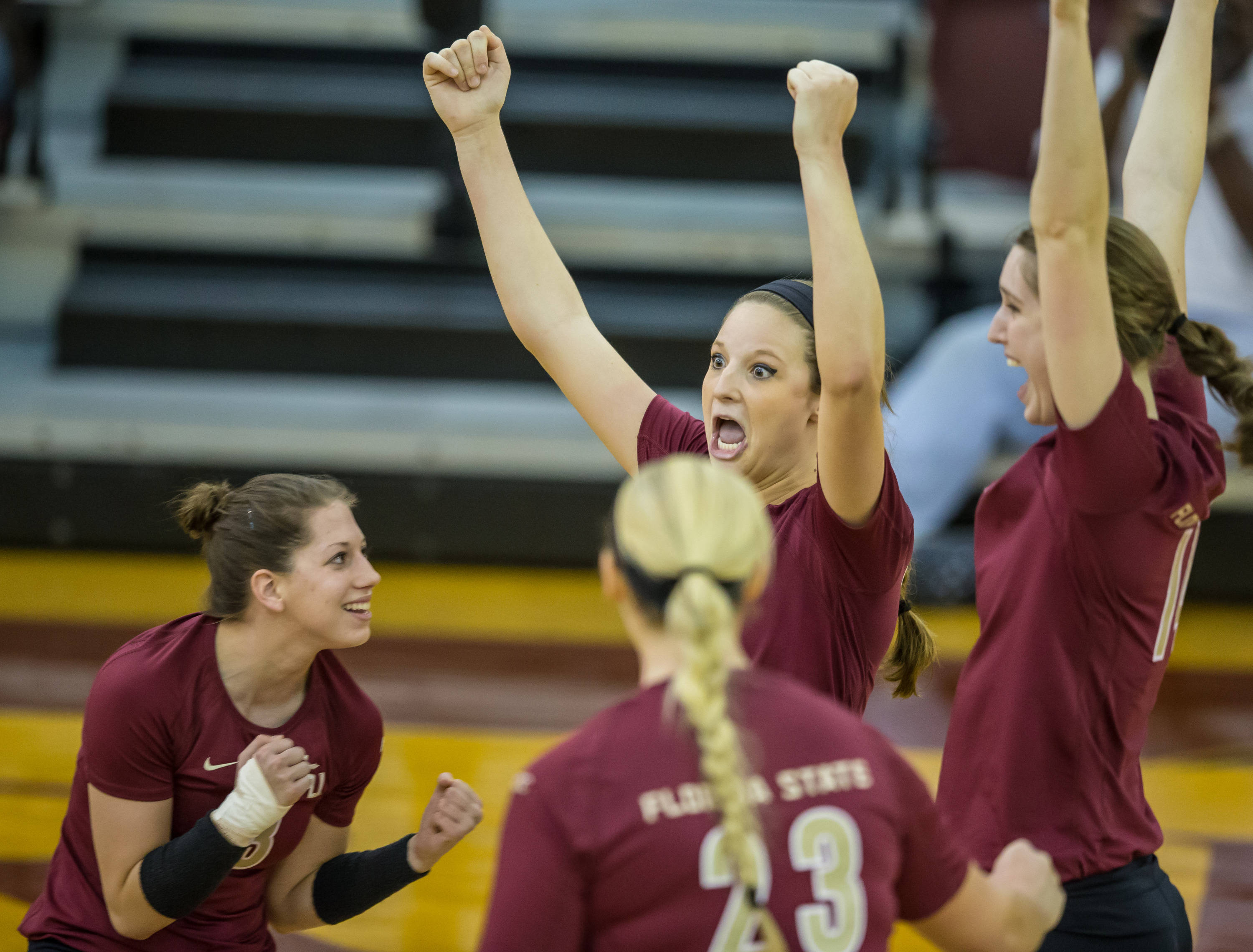 Laura Dadowski (13), Nicole Walch (5), and teammates celebrate another FSU point.