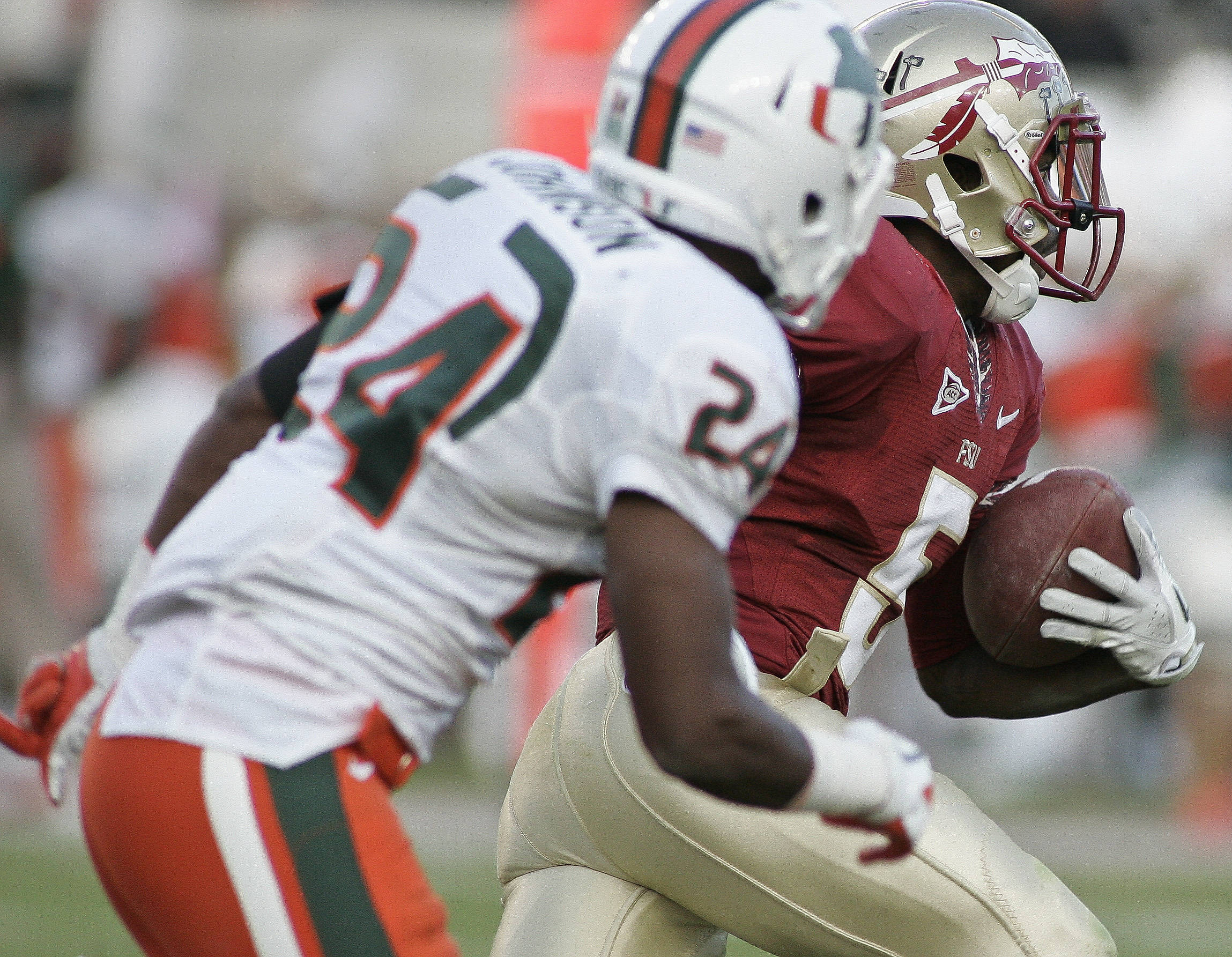 Florida State cornerback Greg Reid, right rear, takes off past Miami defensive back Davon Johnson (24) on an 83-yard punt return for a touchdown during the second quarter of an NCAA college football game on Saturday, Nov. 12, 2011, in Tallahassee, Fla. (AP Photo/Phil Sears)
