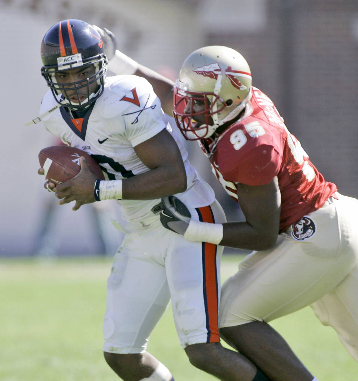 Virginia quarterback Jameel Sewell, left, is sacked in the second quarter of a college football game by Florida State's Kevin McNeil, Saturday, Nov. 4, 2006, in Tallahassee, Fla. (AP Photo/Phil Coale)