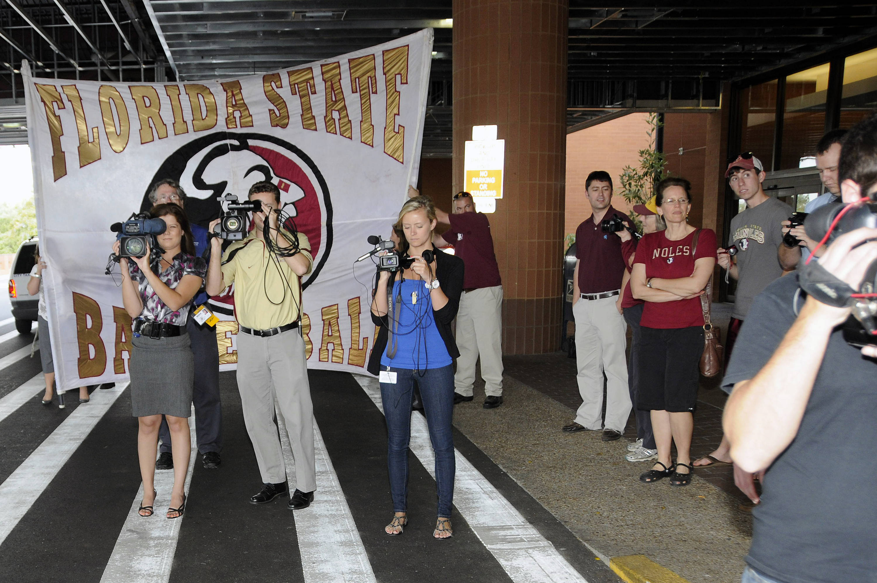 Media and fans await the Seminole team bus at the Tallahassee Airport