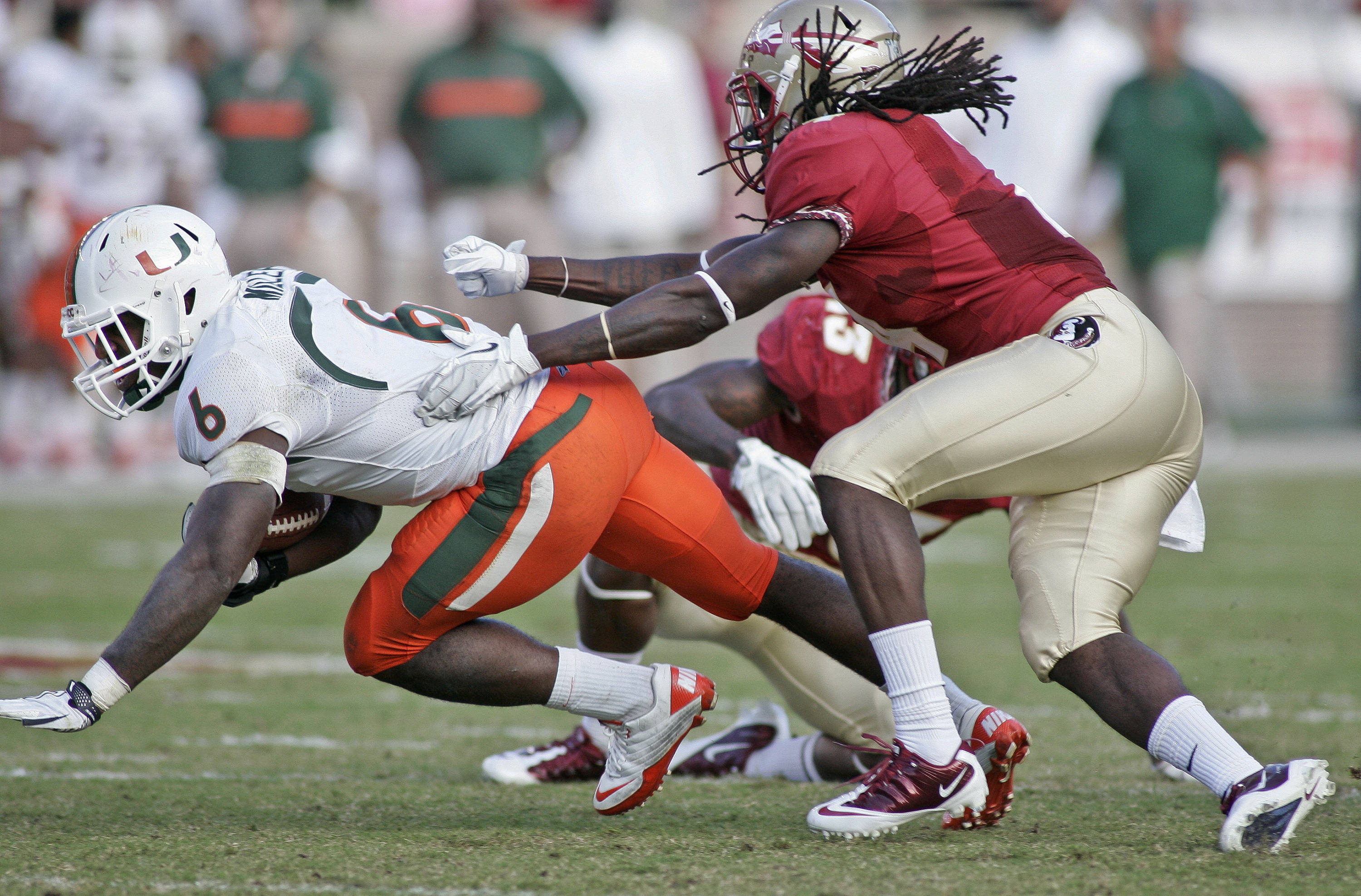 Miami running back Lamar Miller (6) dives for a first down as Florida State safety Terrance Parks (4) pursues during the second quarter of an NCAA college football game on Saturday, Nov. 12, 2011, in Tallahassee, Fla. (AP Photo/Phil Sears)