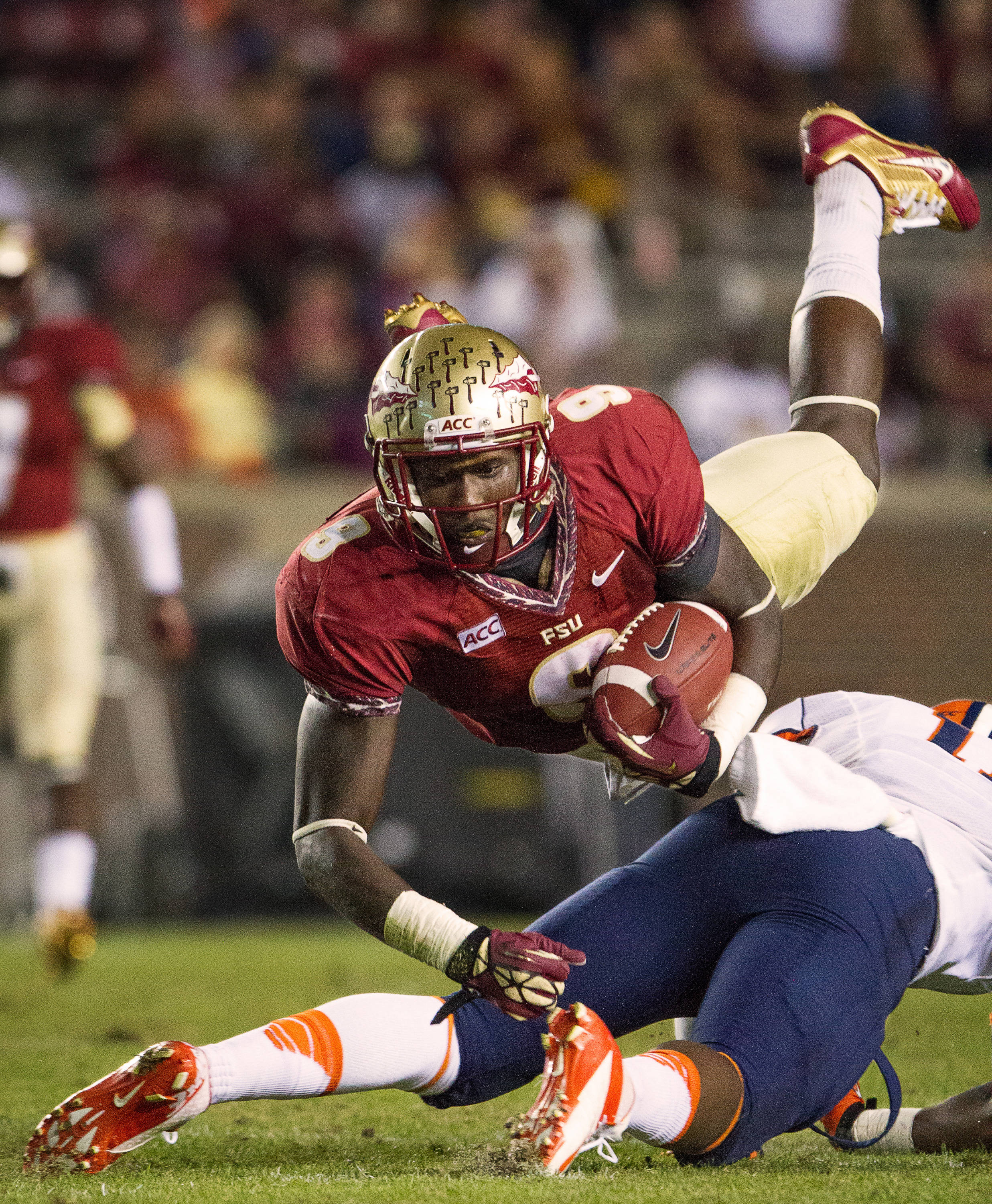 Karlos Williams (9) flies through the air after taking a hit during FSU Football's 59-3 win over Syracuse on Saturday, November 16, 2013 in Tallahassee, Fla. Photo by Mike Schwarz.