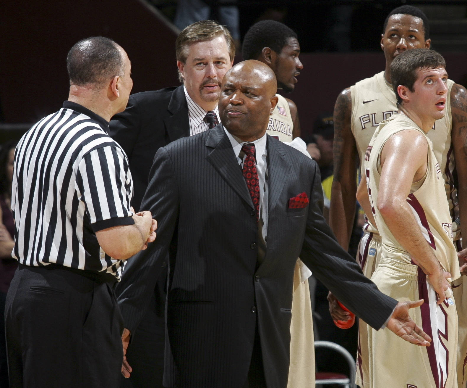 Florida State head coach Leonard Hamilton discusses an intentional foul call on Florida State's Xavier Gibson, right, with a referee during the first half of an NCAA college basketball game against Virginia on Saturday, Feb. 4, 2012, in Tallahassee, Fla. (AP Photo/Phil Sears)