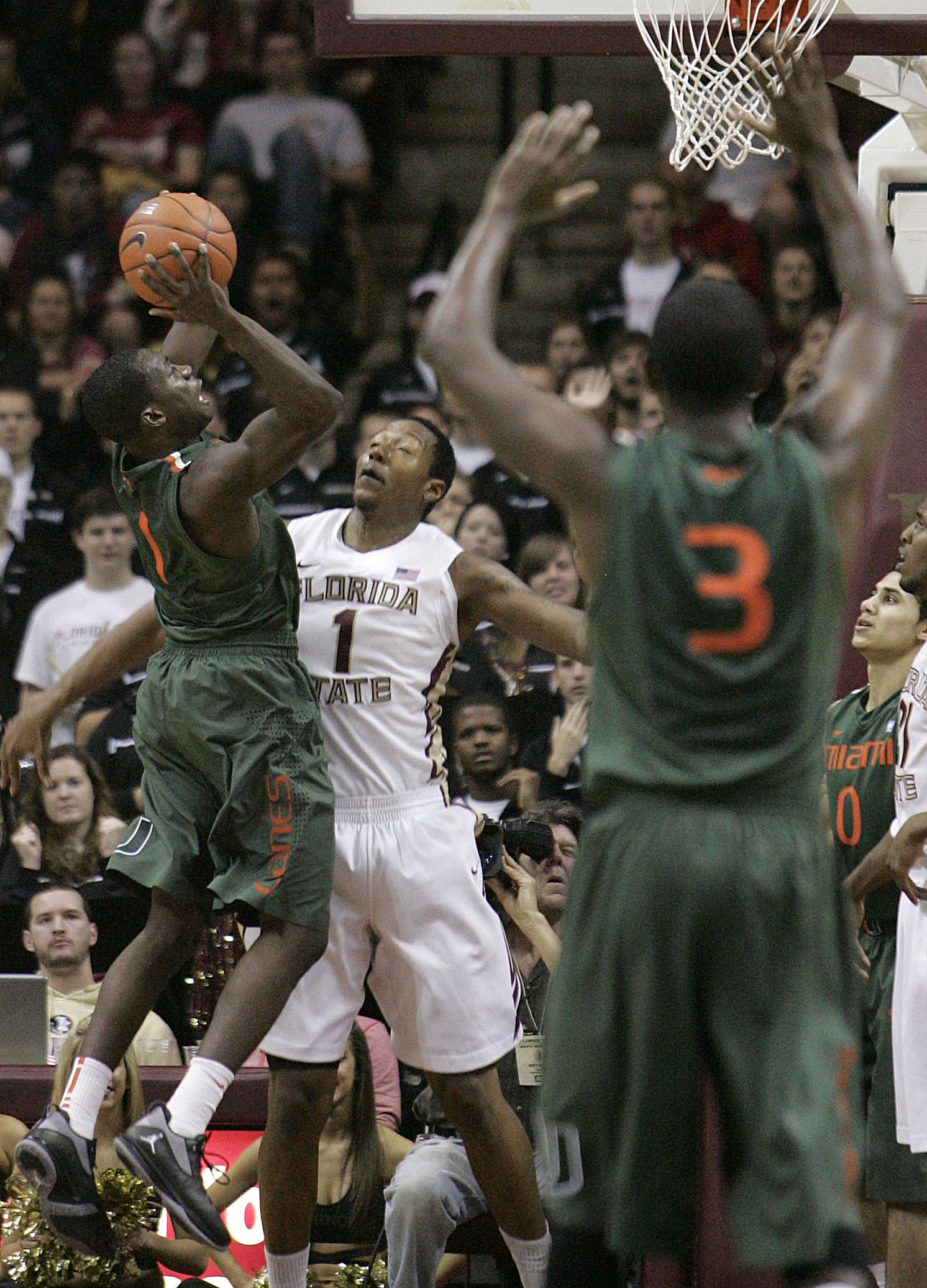 Miami's Durand Scott attempts a shot over the defense of Florida State's Xavier Gibson in the second half of an NCAA college basketball game on Saturday, Feb. 11, 2012 in Tallahassee, Fla.(AP Photo/Steve Cannon)