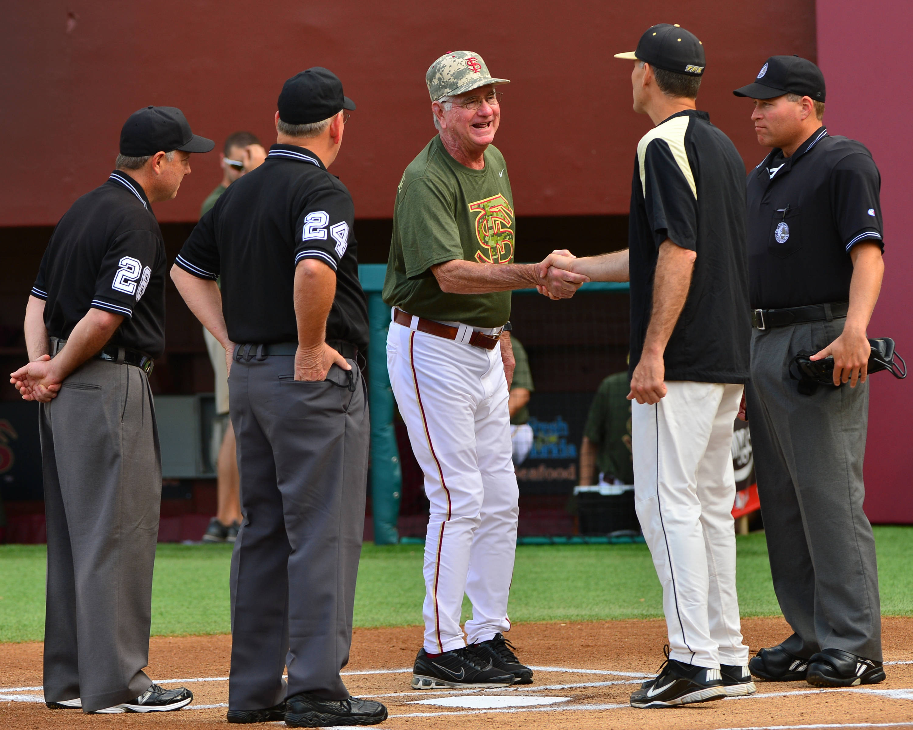 Head coach Mike Martin meets with Wake Forest head coach Tom Walter and the umpires.