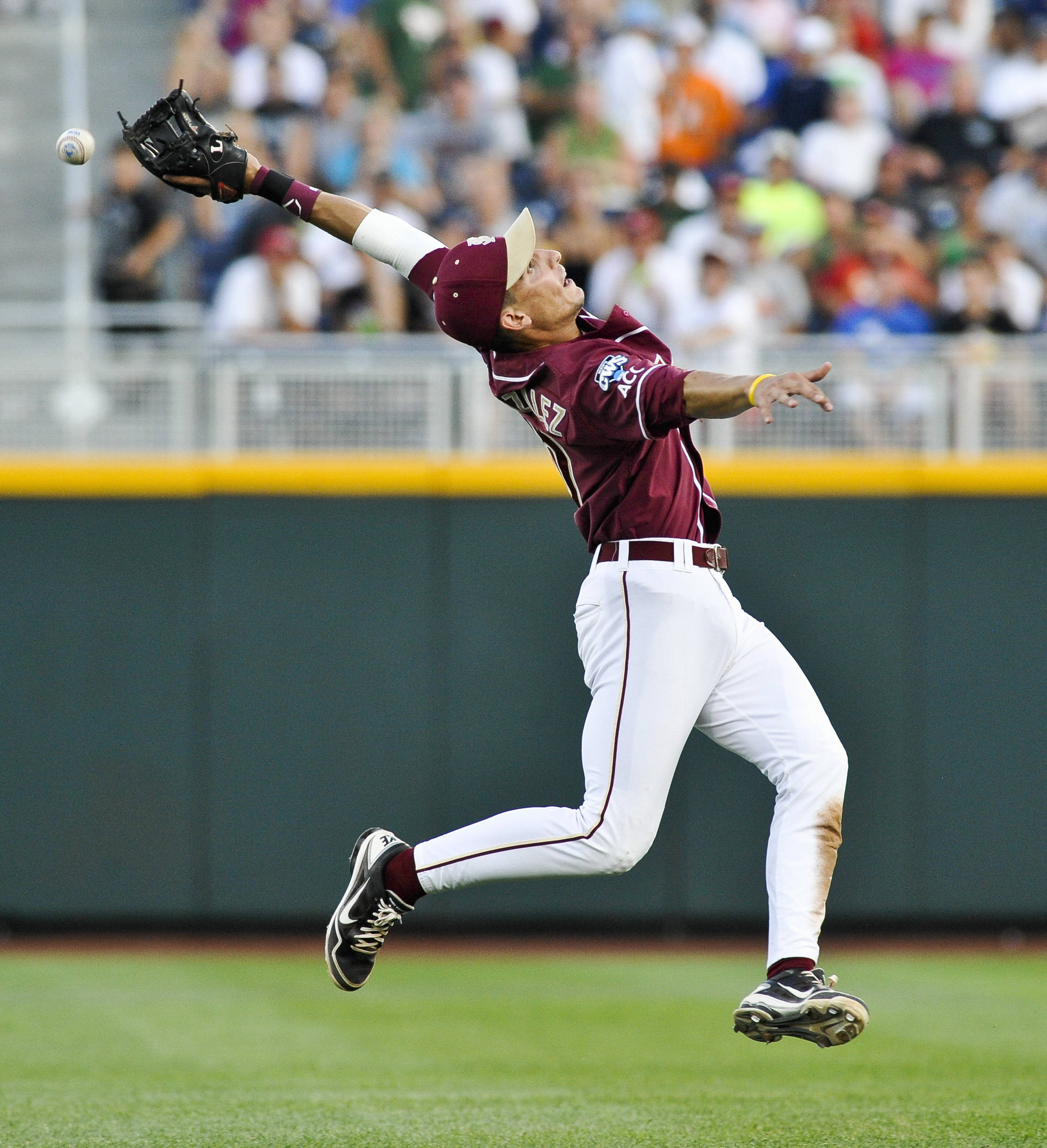 Florida State shortstop Justin Gonzalez can't reach the ball, hit for a single by UCLA's Beau Amaral, in the fourth inning. (AP Photo/Eric Francis)