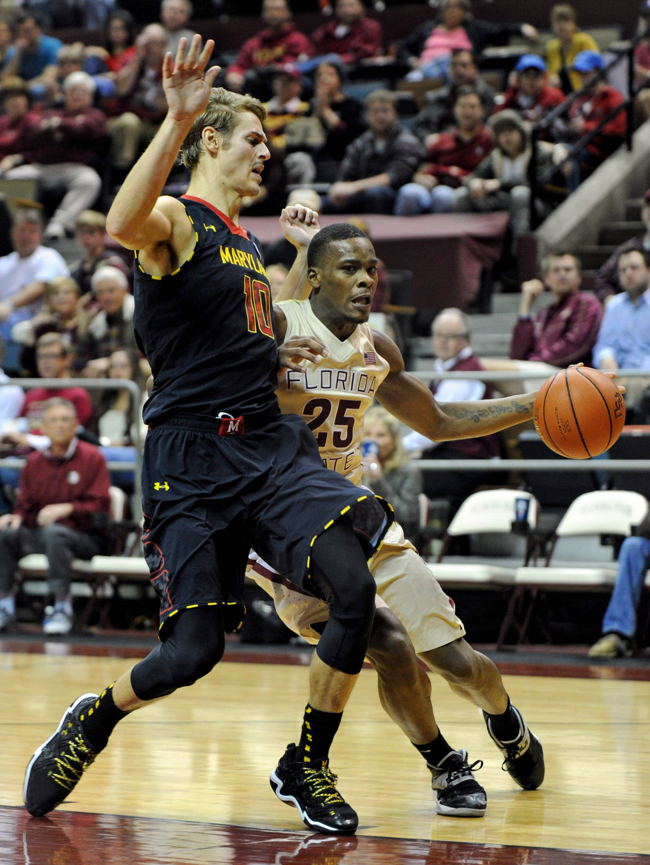 Jan 12, 2014; Tallahassee, FL, USA; Florida State Seminoles guard Aaron Thomas (25) moves the ball past Maryland Terrapins forward Jake Layman (10) during the first half at Donald L. Tucker Center. Mandatory Credit: Melina Vastola-USA TODAY Sports