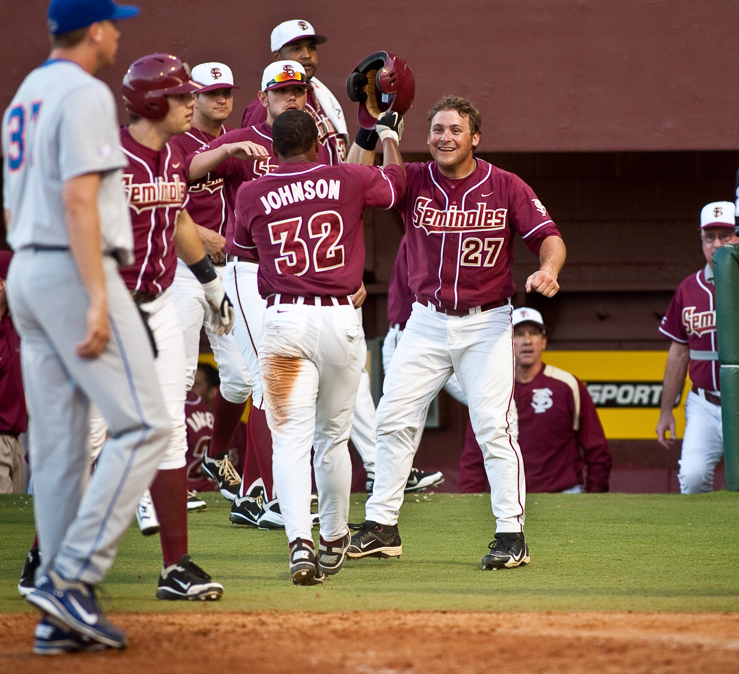 Sherman Johnson (32) is greeted by teammates after scoring on a wild pitch