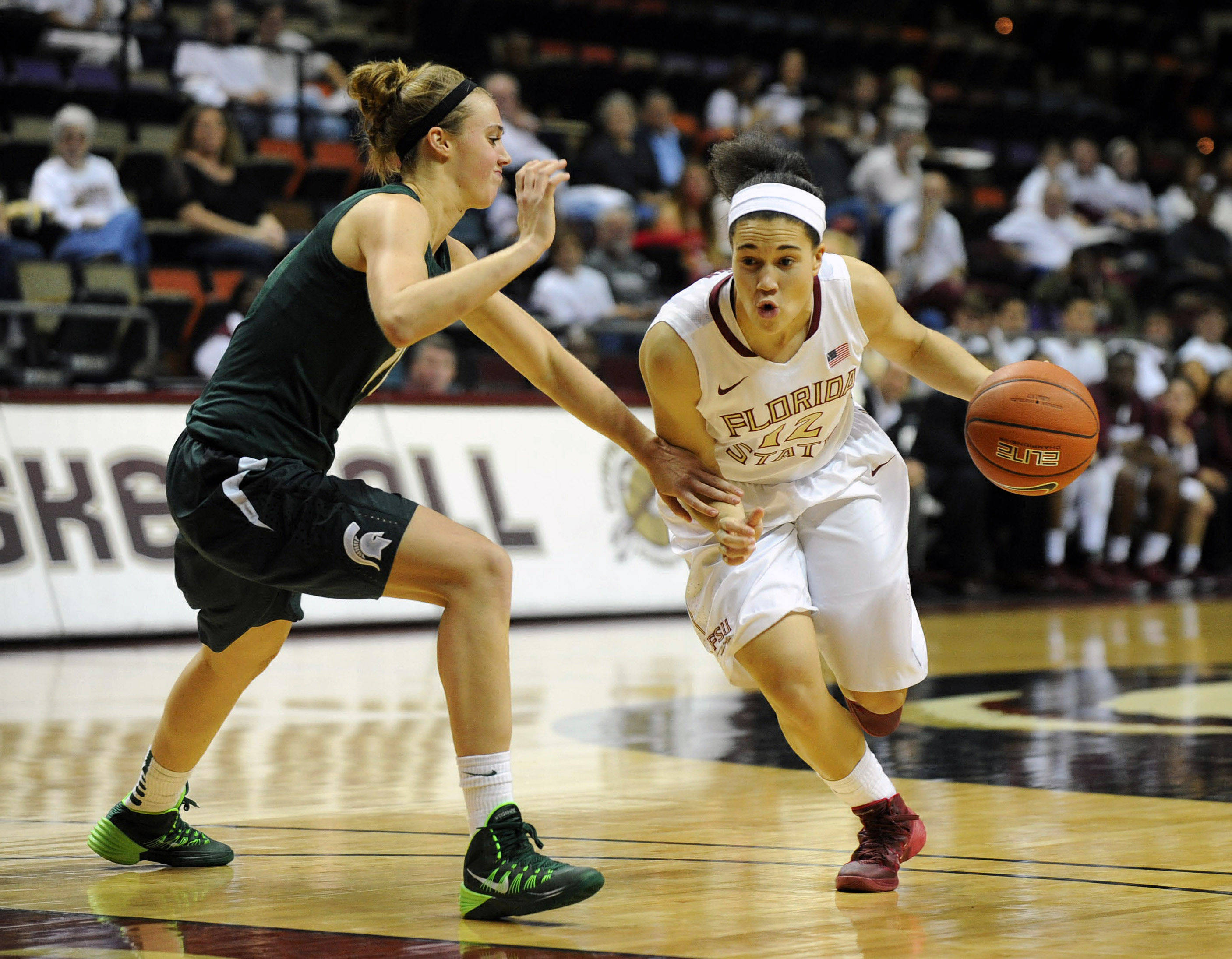 Dec 4, 2013; Tallahassee, FL, USA; Florida State Seminoles guard Brittany Brown (12) moves past Michigan State Spartans forward Annalise Pickrel (11) during the game at the Donald L. Tucker Center. Mandatory Credit: Melina Vastola-USA TODAY Sports