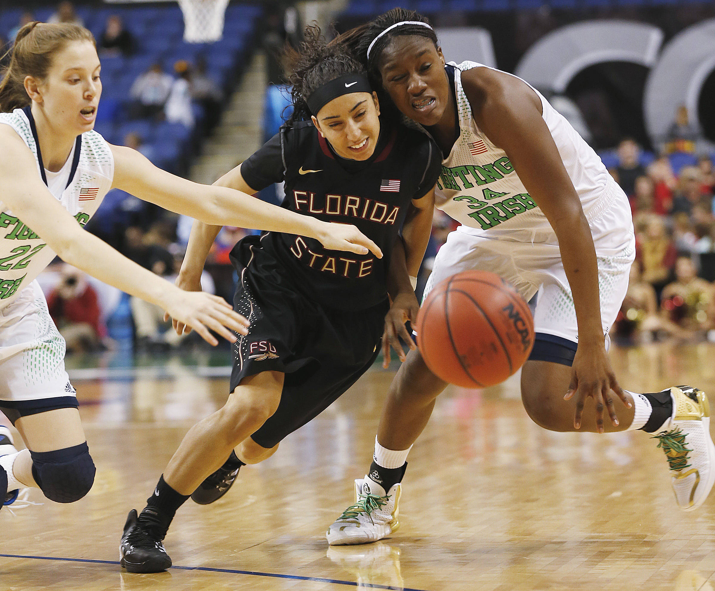 Mar 7, 2014; Greensboro, NC, USA; Notre Dame Fighting Irish players Madison Cable (22) and Markisha Wright (34) battle Seminoles guard Cheetah Delgado (5) for a loose ball. Ellen Ozier-USA TODAY Sports