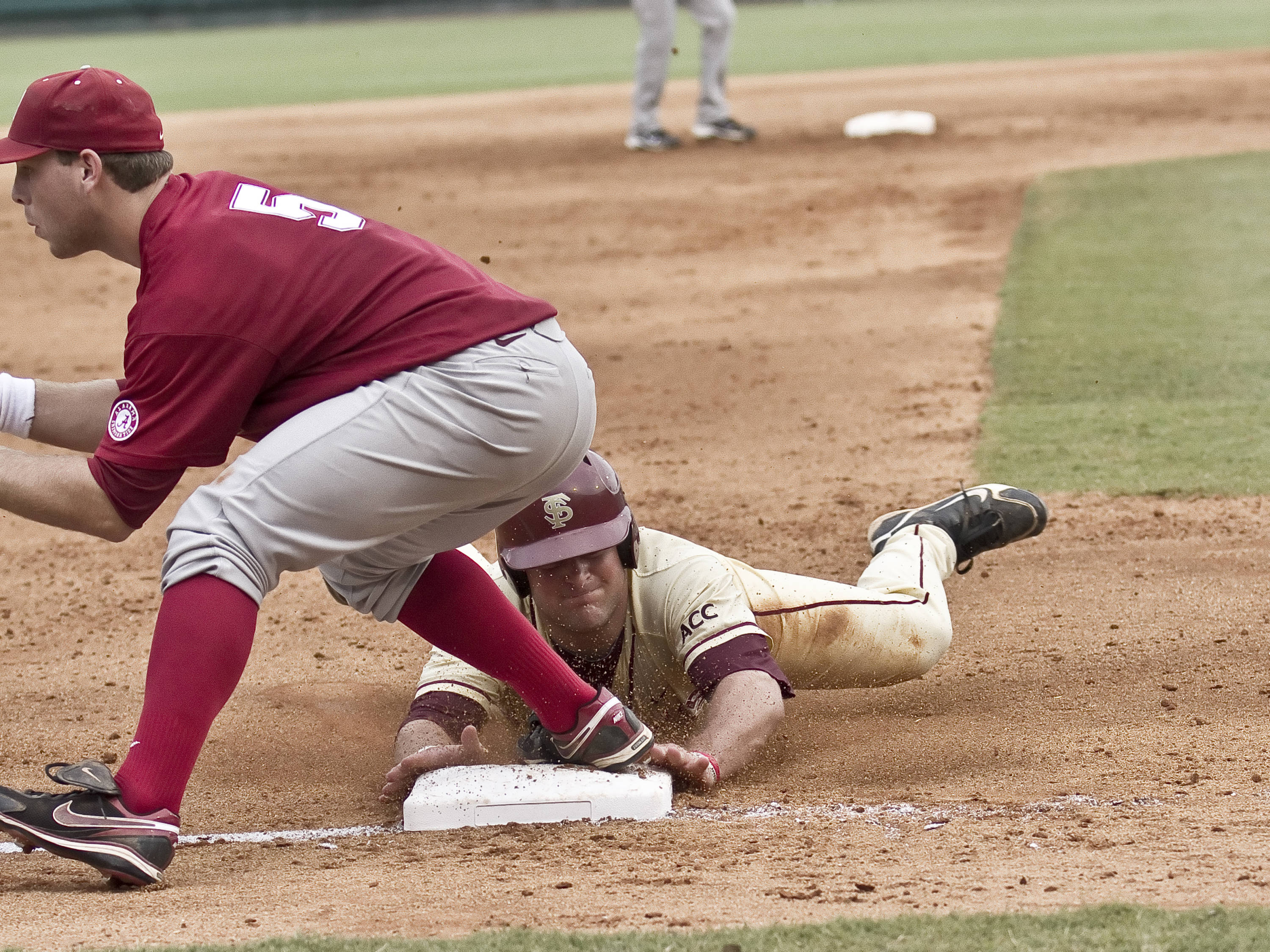 Stuart Tapley (27) sliding and beating the throw at third base