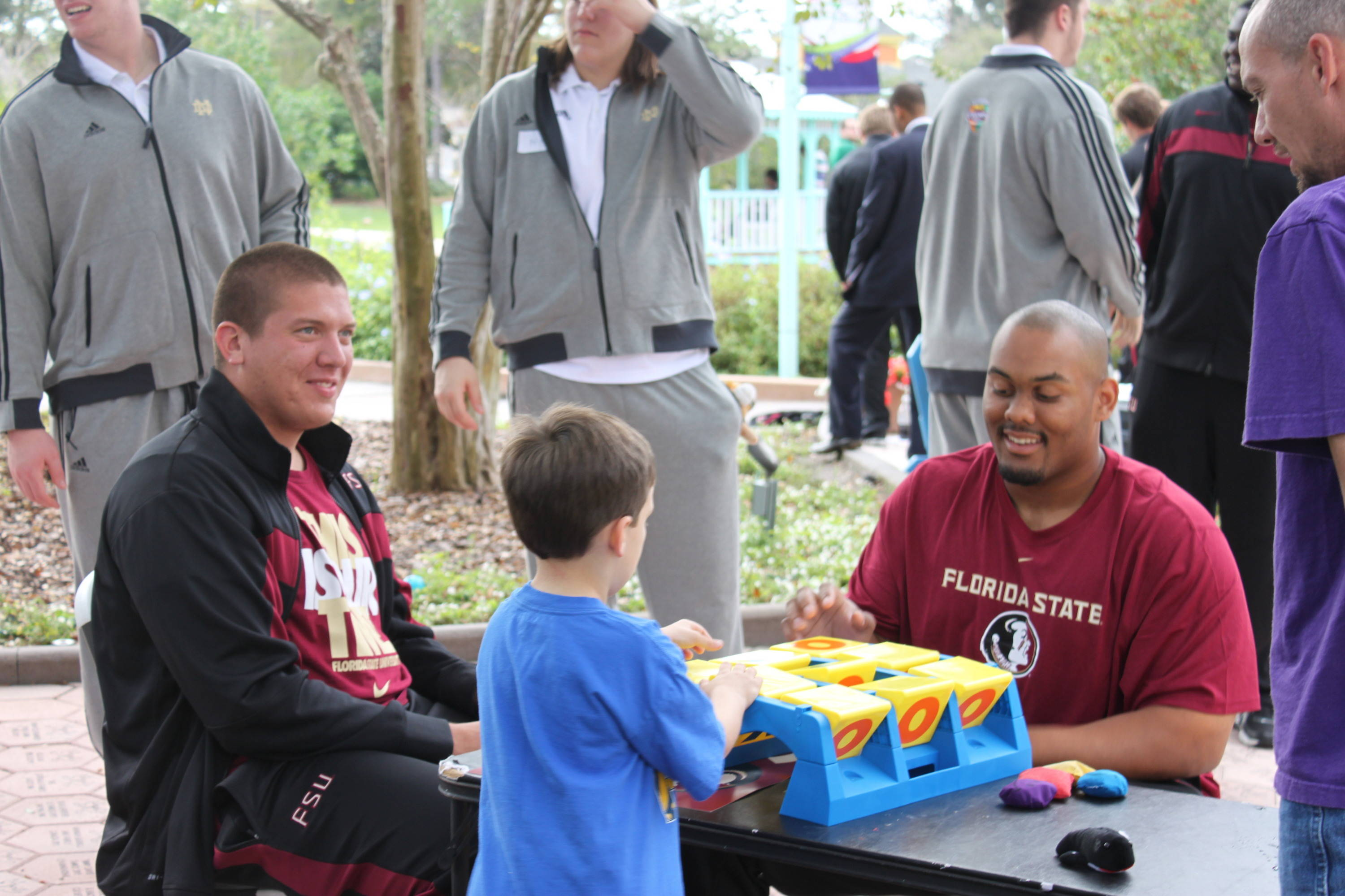 Andrew Datko and Rhonne Sanderson share a laugh during a game of Tic-Tac-Toe with a young boy.