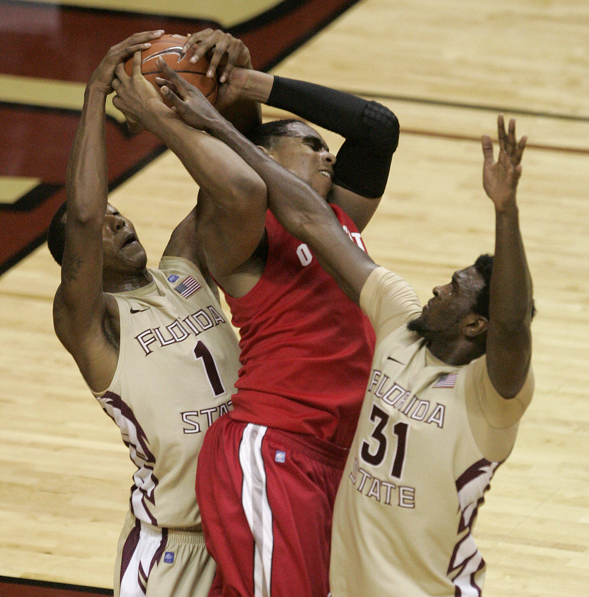 Ohio State's Jared Sullinger is tied up by Florida State's Xavier Gibson, left and Chris Singleton in the second half.(AP Photo/Steve Cannon)