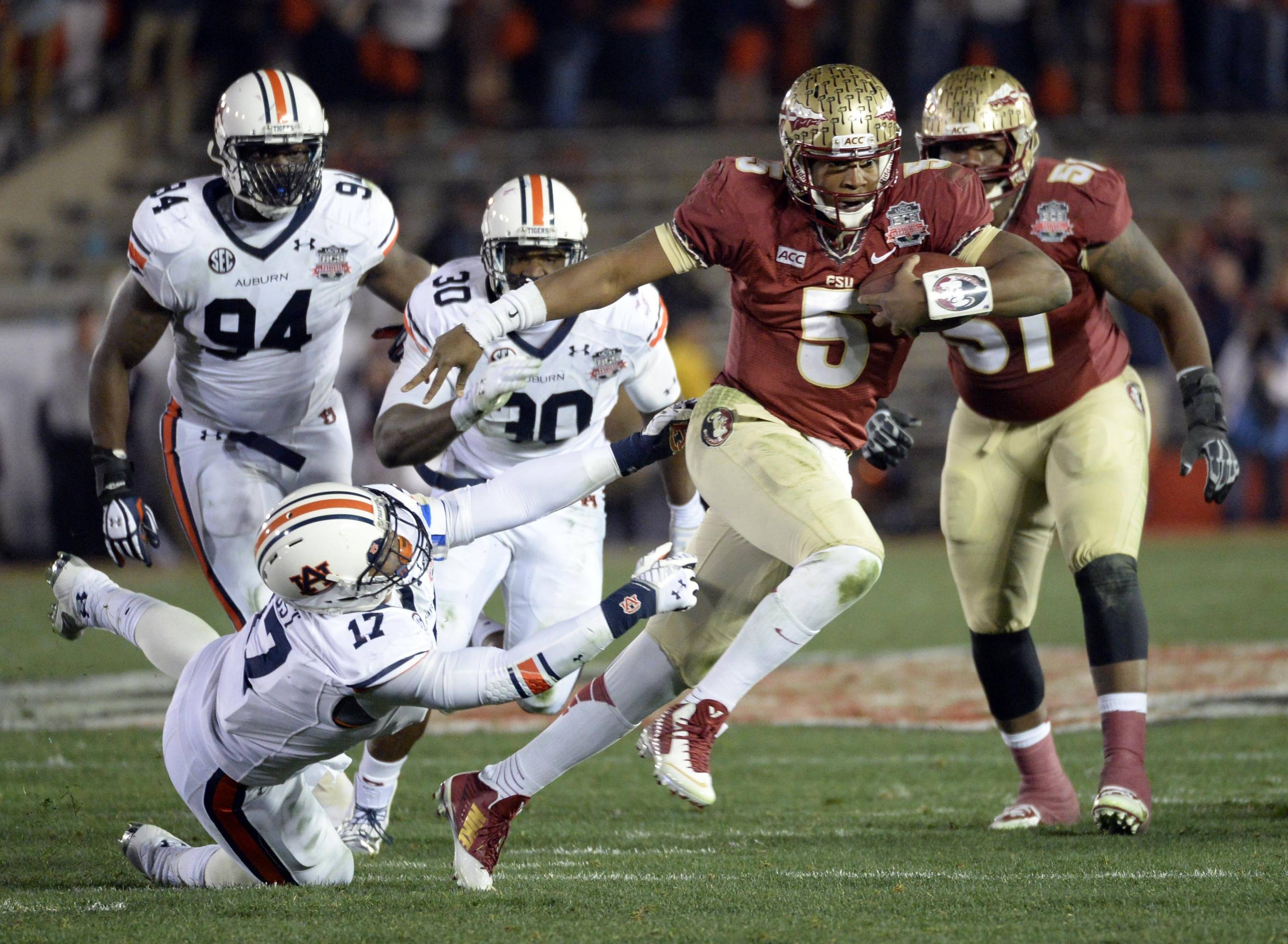 Jan 6, 2014; Pasadena, CA, USA; Florida State Seminoles quarterback Jameis Winston (5) escapes the tackle from Auburn Tigers linebacker Kris Frost (17)during the first half of the 2014 BCS National Championship game at the Rose Bowl.  Mandatory Credit: Richard Mackson-USA TODAY Sports