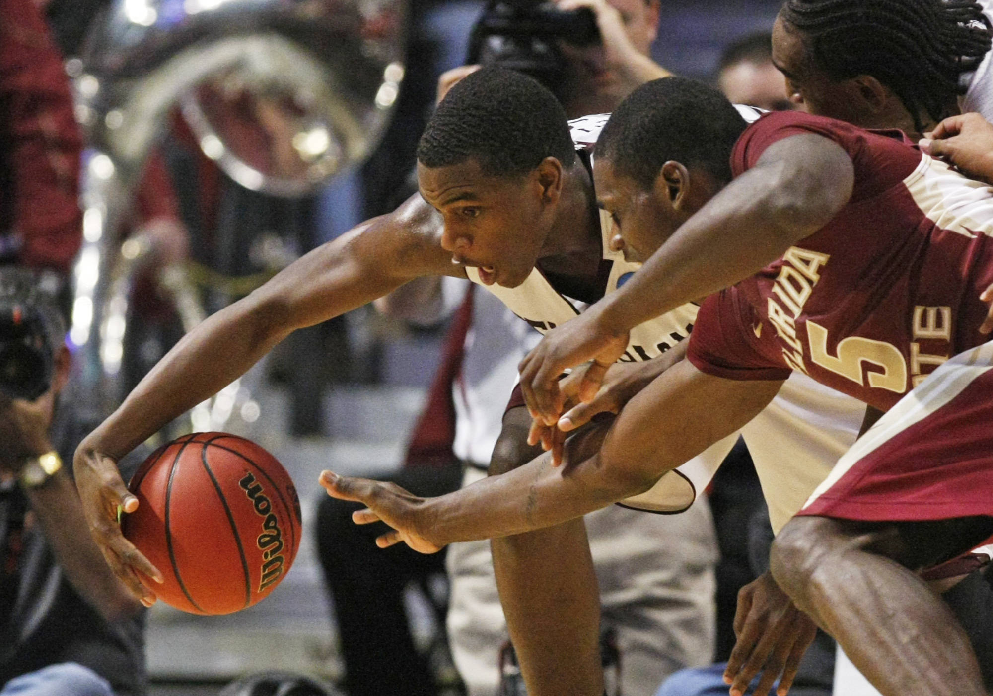 Texas A&M's Khris Middleton and Florida State's Bernard James scramble for a loose ball in the second half . (AP Photo/Charles Rex Arbogast)