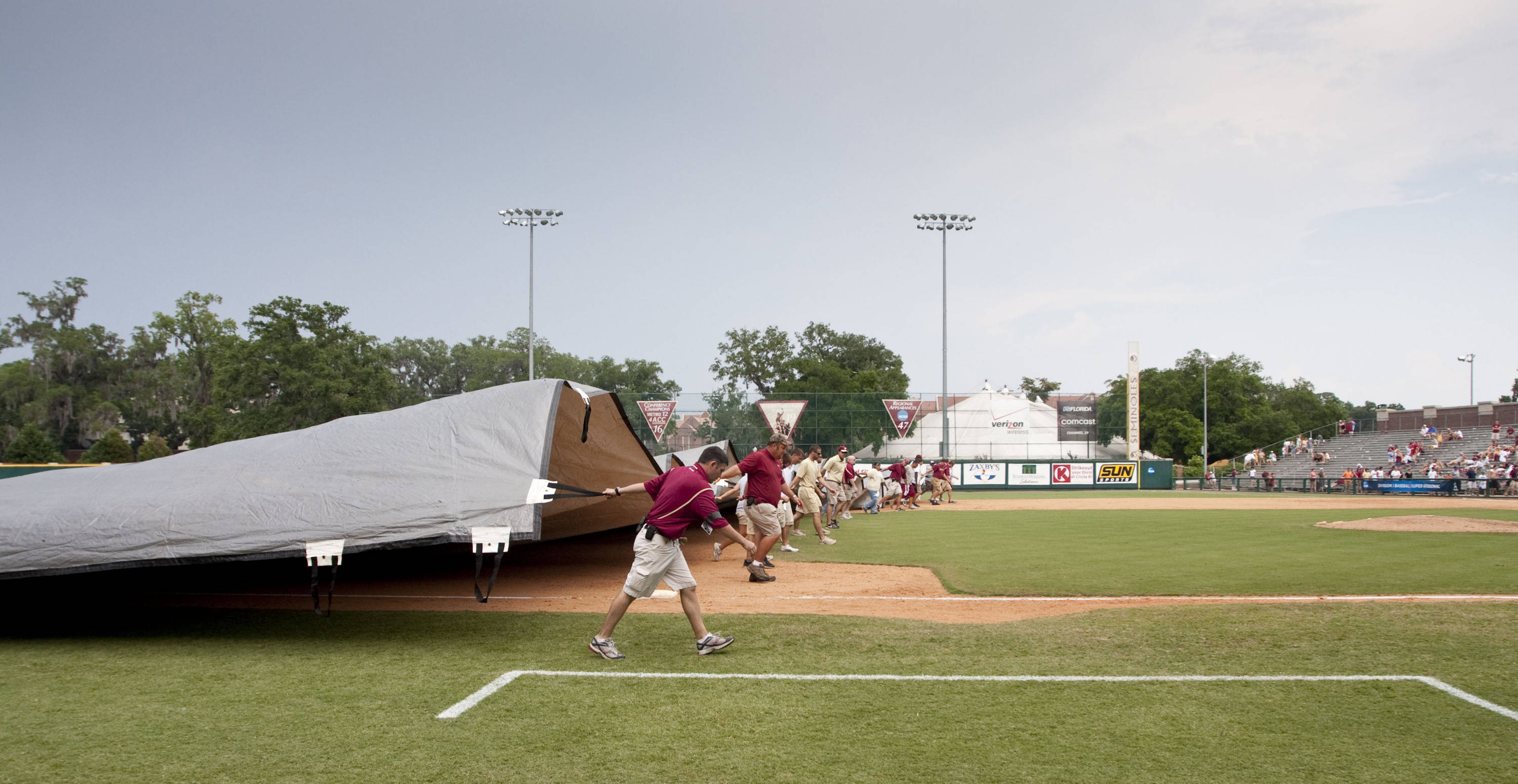 FSU staff cover the infield after the game is delayed due to lightening in the 8th inning.