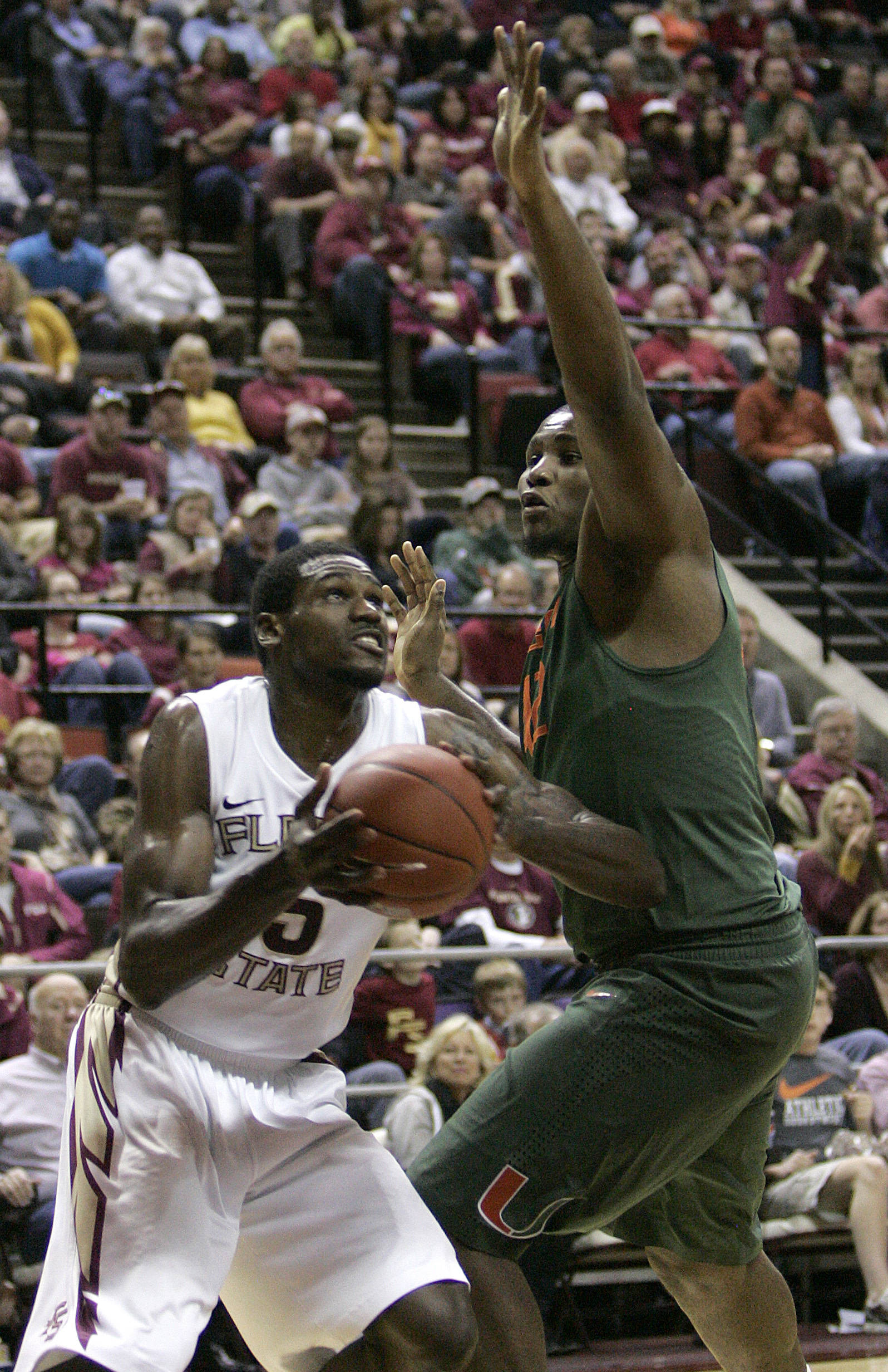 Florida State's Bernard James gets around the defense of Miami's Reggie Johnson to score in the second half of an NCAA college basketball game on Saturday, Feb. 11, 2012 in Tallahassee, Fla.(AP Photo/Steve Cannon)