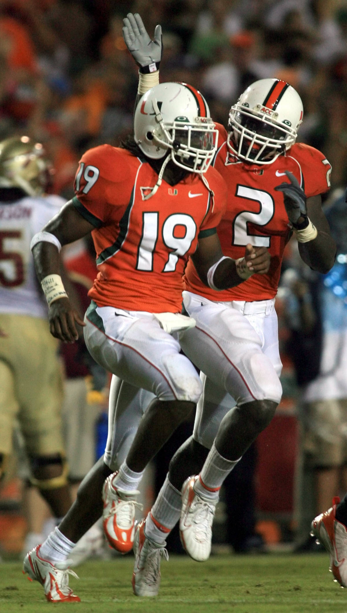Miami safety Brandon Meriweather (19) is congratulated by linebacker Jon Beason after Meriweather intercepted a pass during the second quarter of football against Florida St., Monday, Sept. 4, 2006 at the Orange Bowl in Miami. (AP Photo/Luis M. Alvarez)