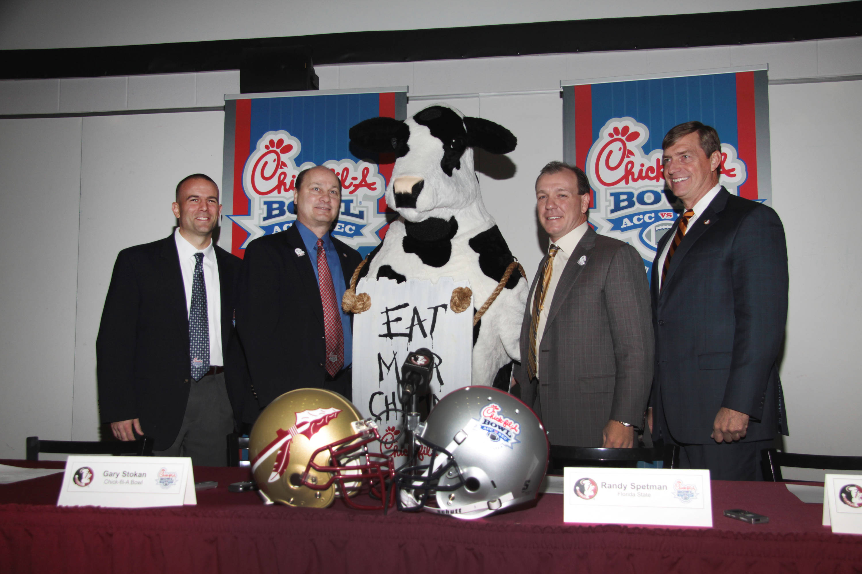Chick-fil-A Executives, Director of Athletics Randy Spetman and Jimbo Fisher pose for a picture with the Chick-fil-A cow after Thursday's press conference.