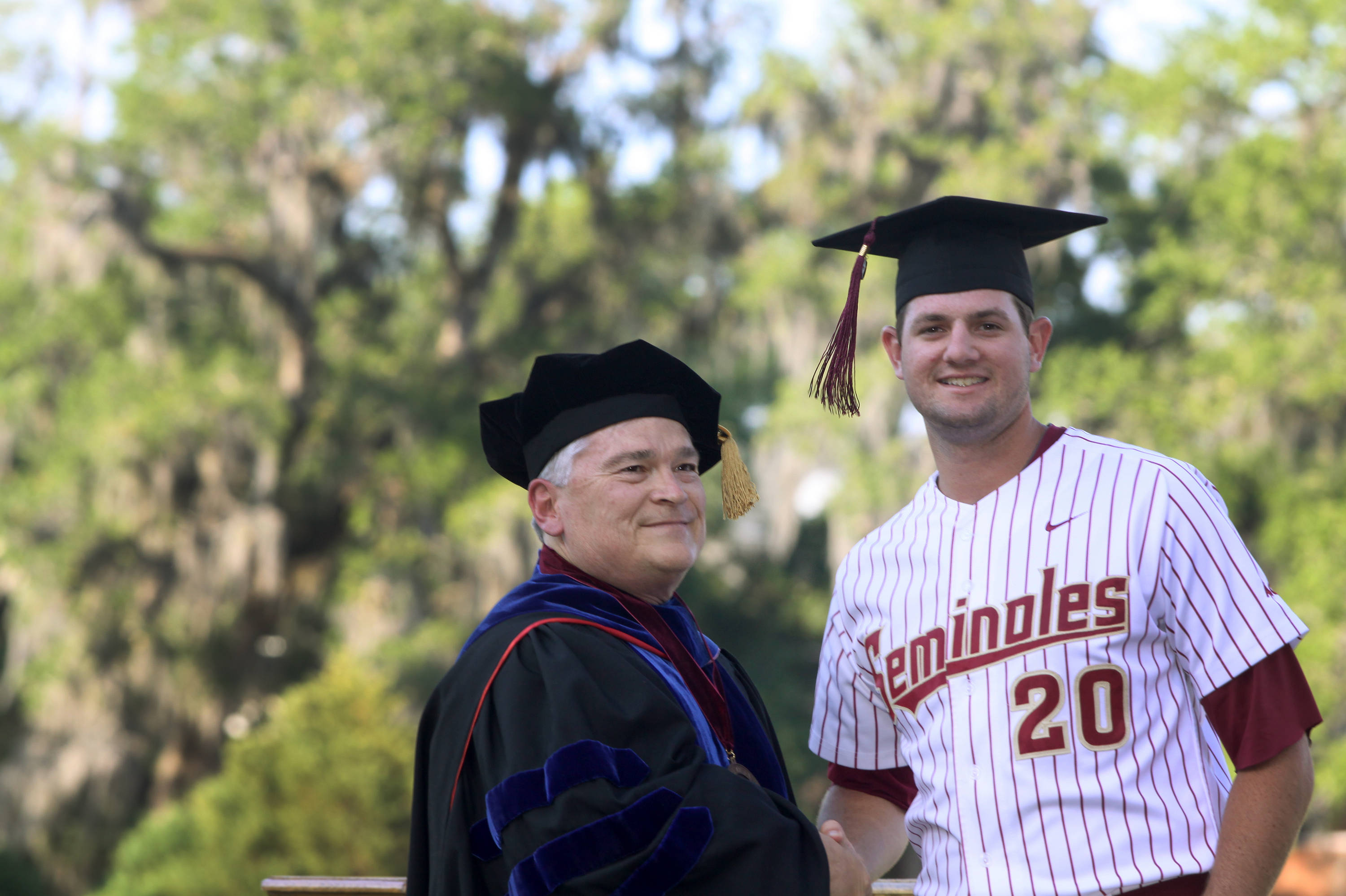2011 Spring Graduation Ceremony held at Dick Howser Stadium to honor the graduating baseball seniors. Daniel Bennett (20) with President Barron