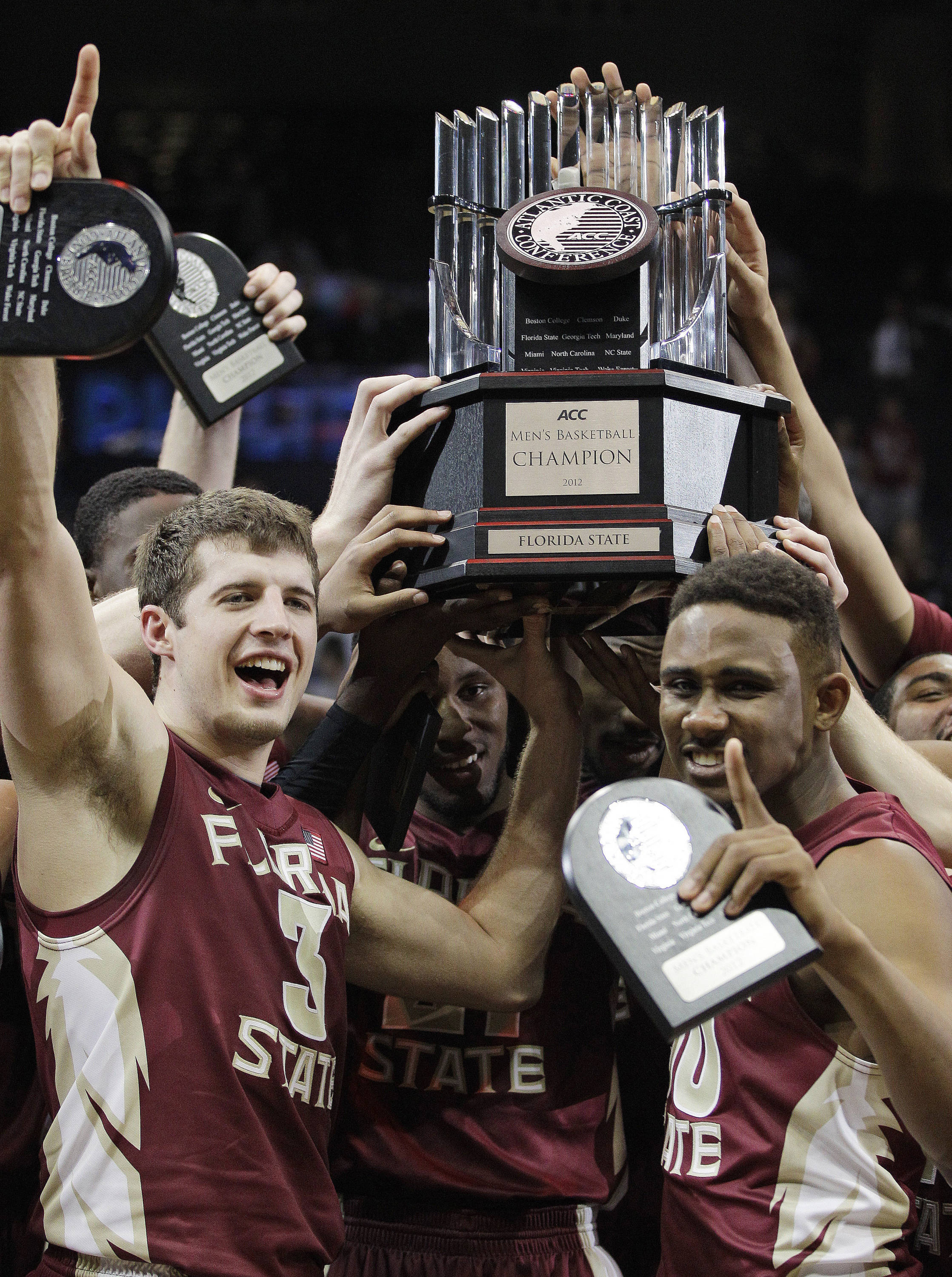 Florida State guard Luke Loucks and guard Ian Miller hold the Atlantic Coast Conference tournament trophy. (AP Photo/Chuck Burton)