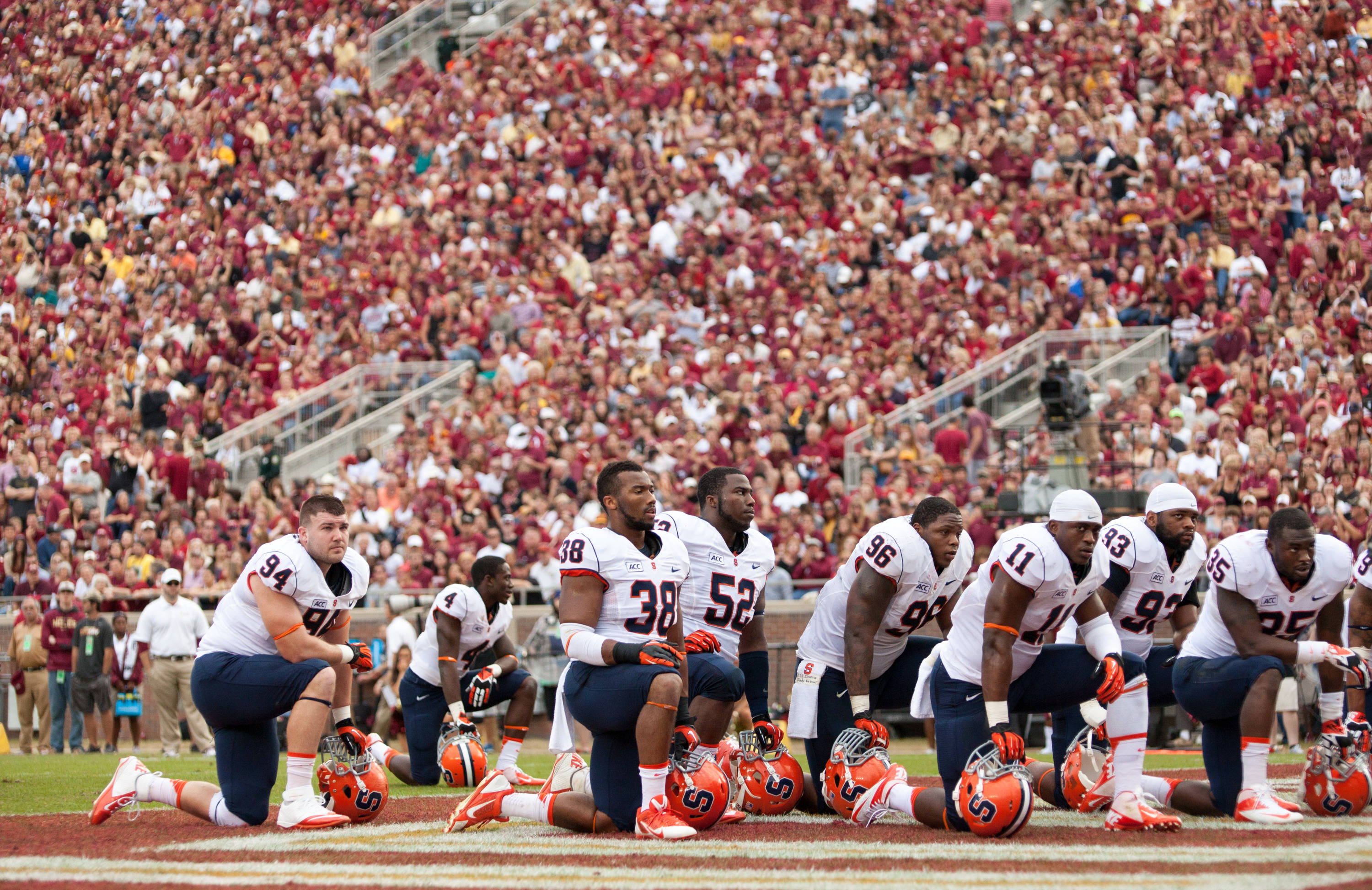 Syracuse players take a knee as injured teammateJulian Whigham is loaded on to a stretcher during FSU Football's 59-3 win over Syracuse on Saturday, November 16, 2013 in Tallahassee, Fla. Photo by Mike Schwarz.