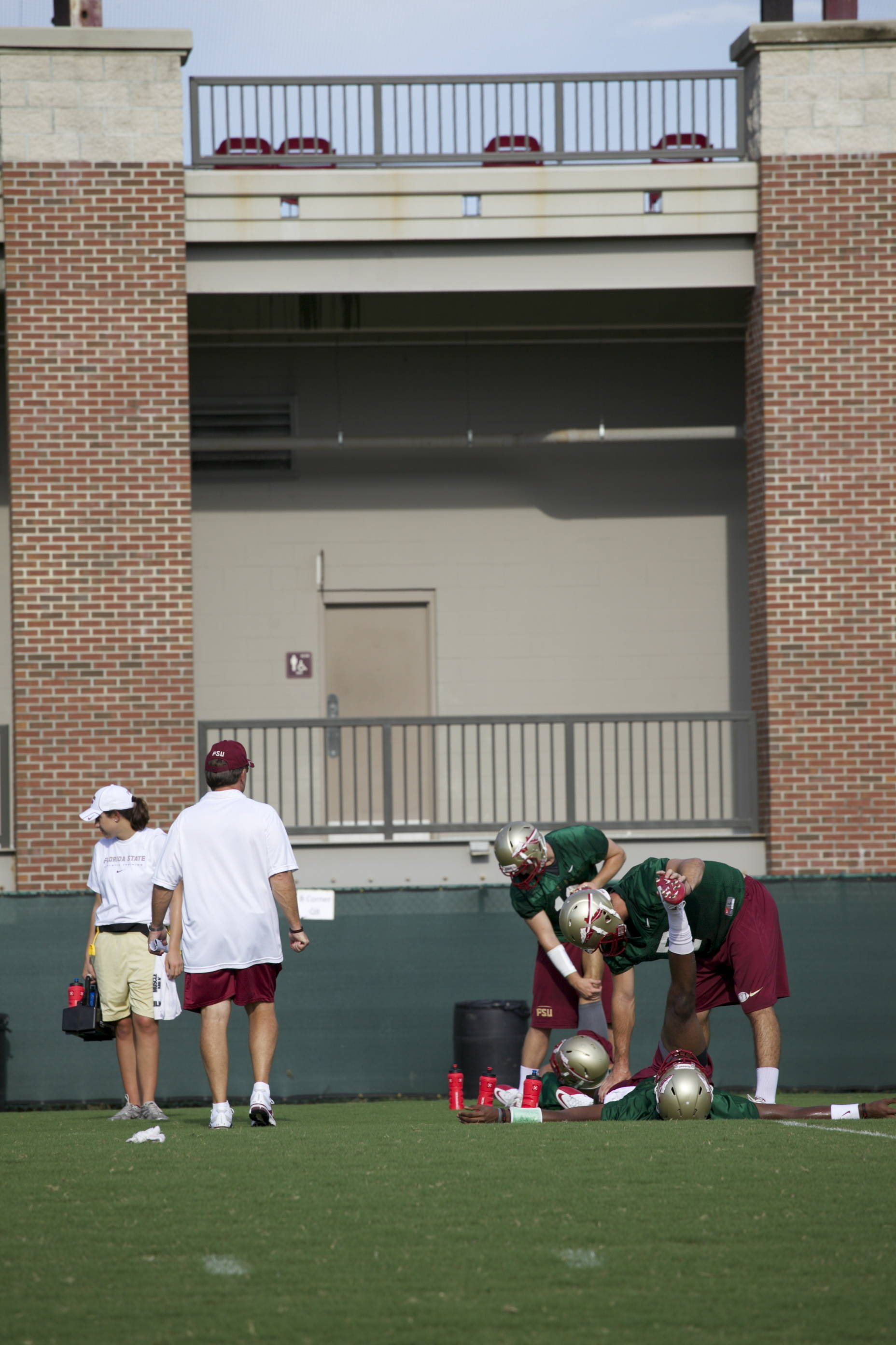 Coach Fisher helping the team stretch before practice.
