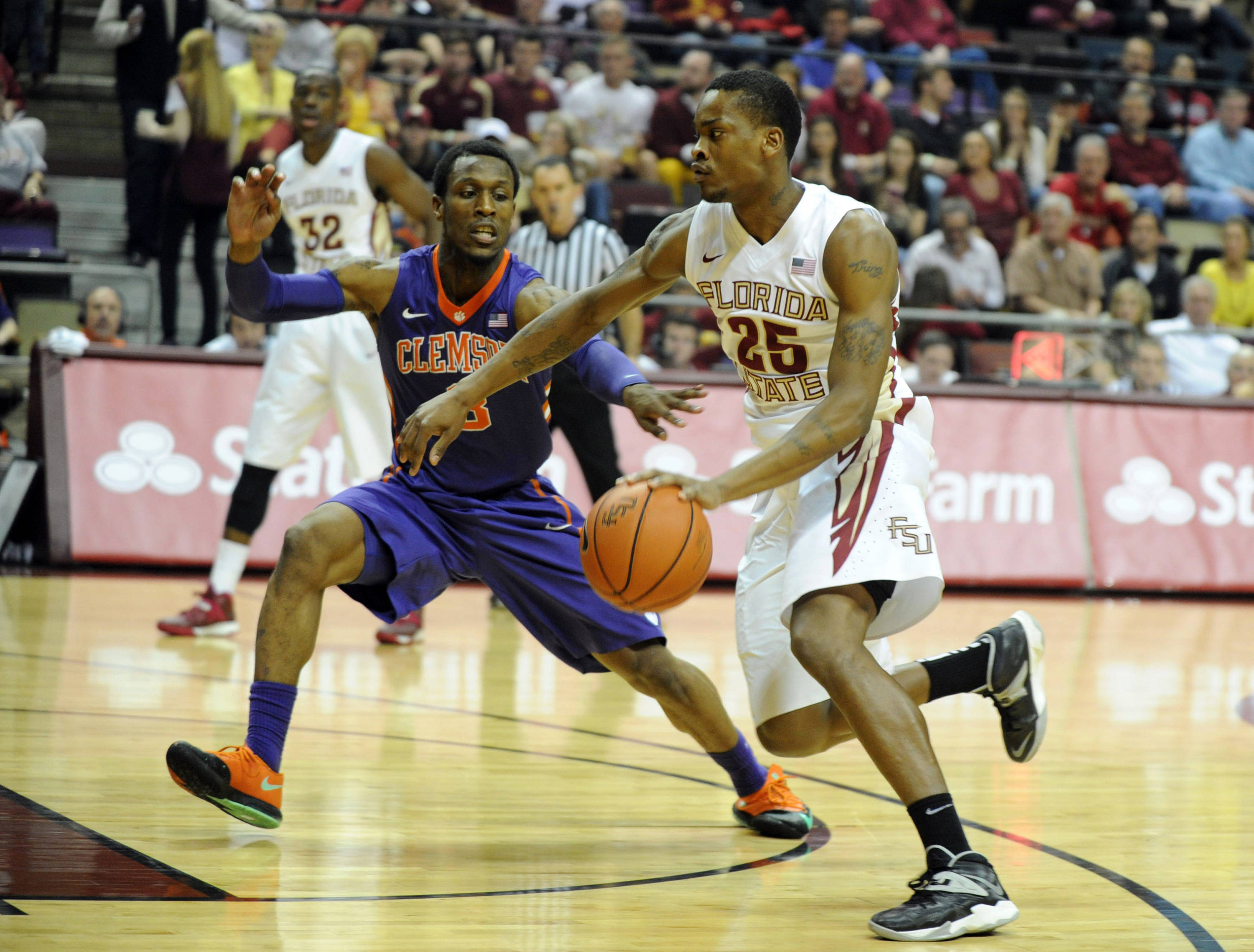 Feb 1, 2014; Tallahassee, FL, USA; Florida State Seminoles guard Aaron Thomas (25) moves the ball past Clemson Tigers guard Adonis Filer (3) during the first half at the Donald L. Tucker Center. Mandatory Credit: Melina Vastola-USA TODAY Sports