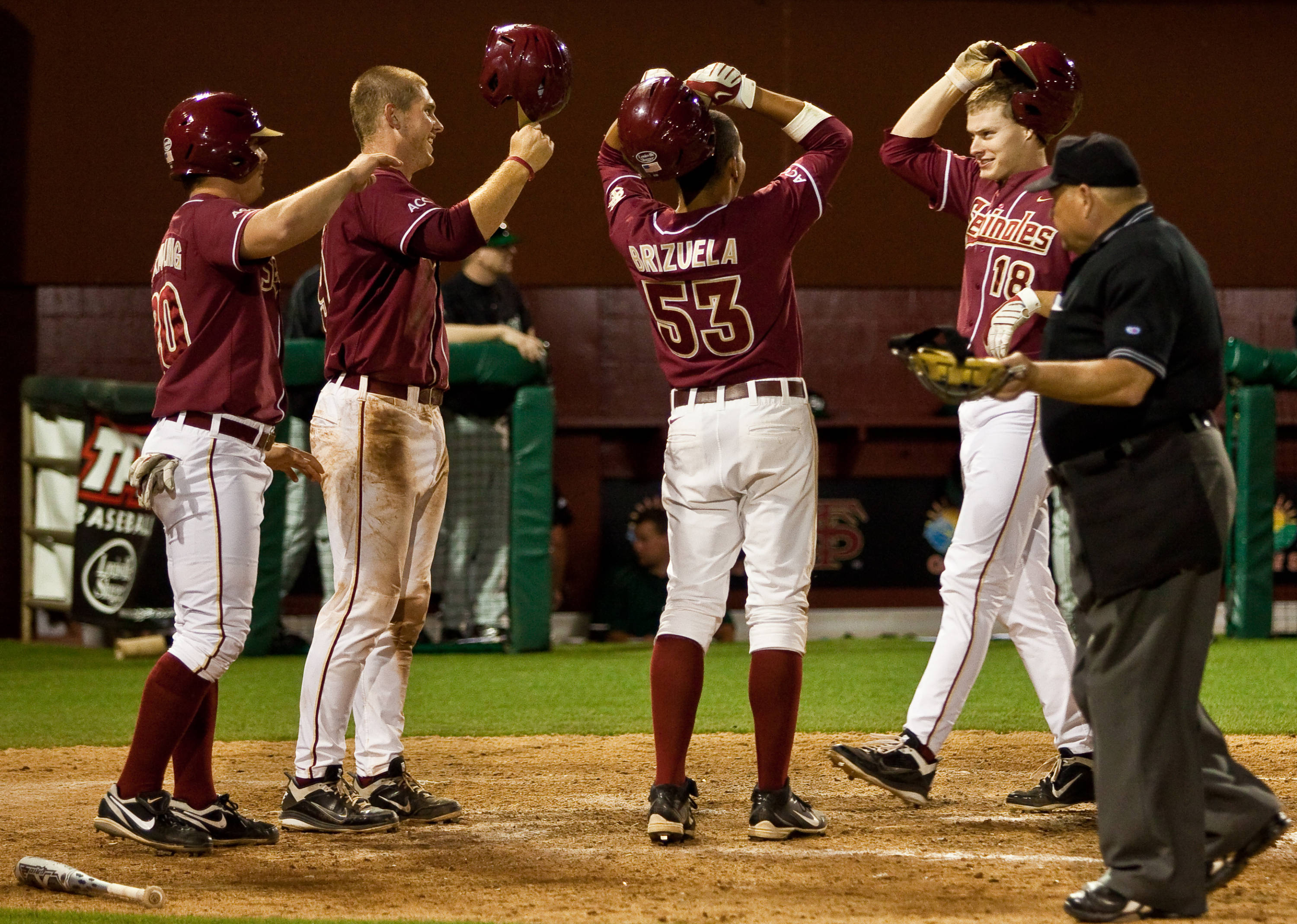 Seth Miller celebrates at home plate with his teammates after connecting on a grand slam in the eighth inning.
