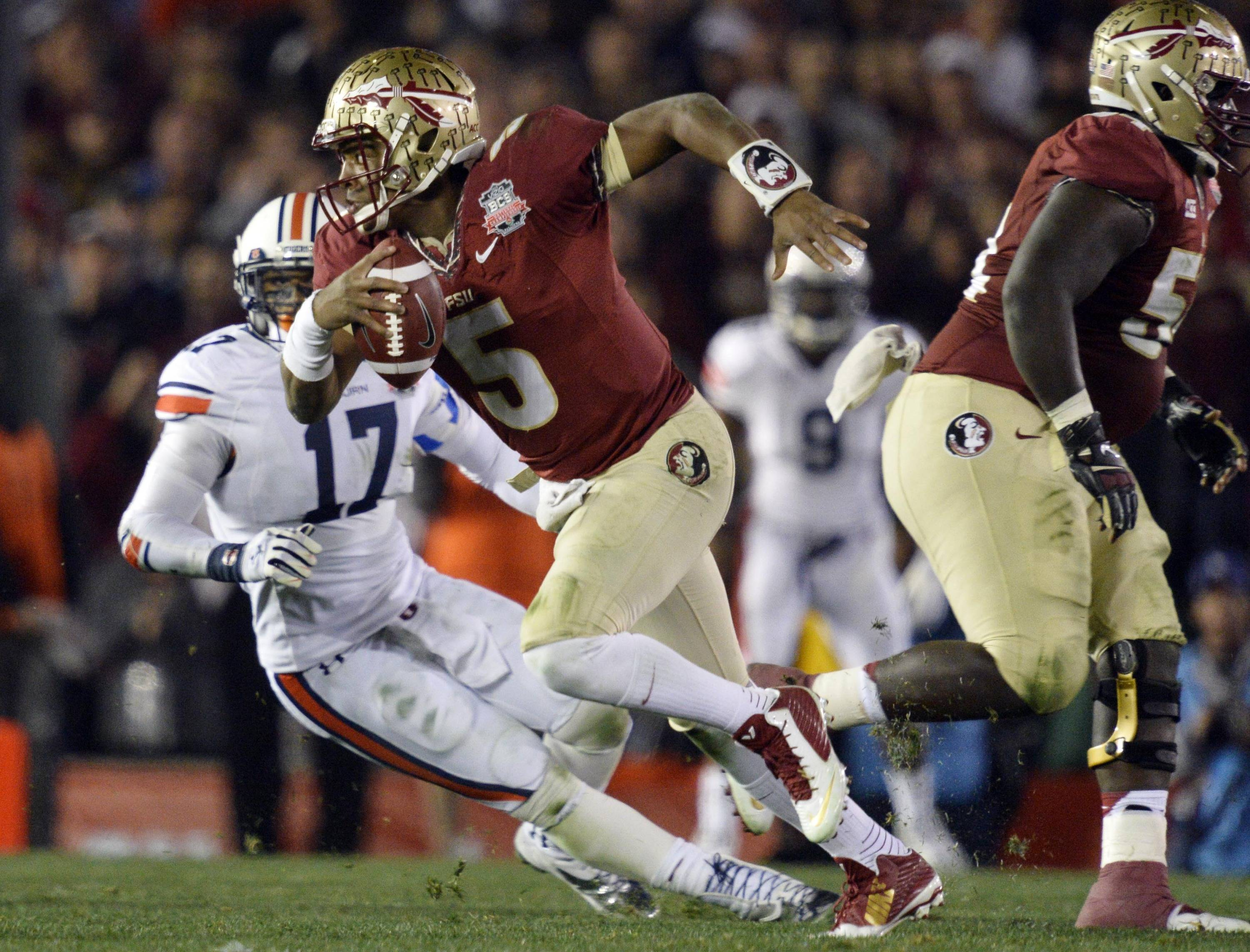 Jan 6, 2014; Pasadena, CA, USA; Florida State Seminoles quarterback Jameis Winston (5) runs past Auburn Tigers linebacker Kris Frost (17) during the first half of the 2014 BCS National Championship game at the Rose Bowl.  Mandatory Credit: Robert Hanashiro-USA TODAY Sports