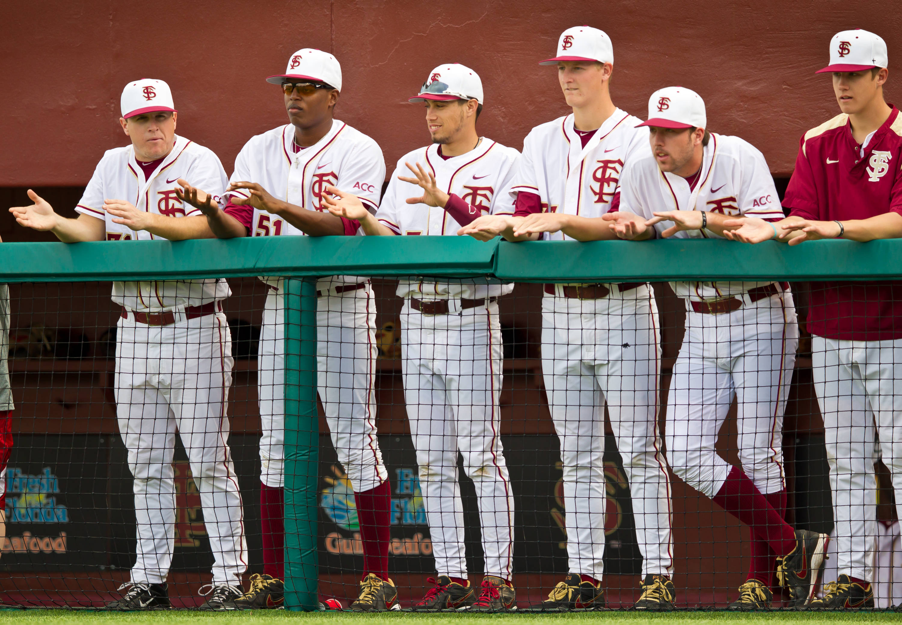 The Seminoles look on from the first base dugout.
