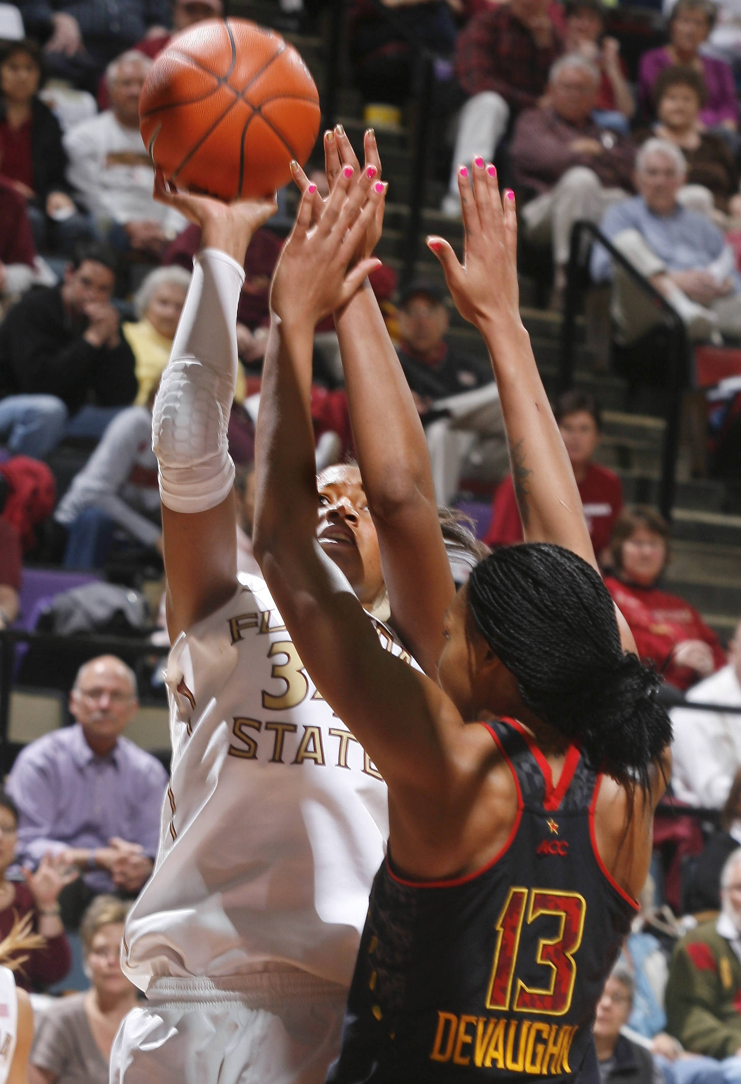 Florida State forward Chelsea Davis (34) is fouled by Maryland center Alicia DeVaughn (13) as she tries a layup in the second half. (AP Photo/Phil Sears)