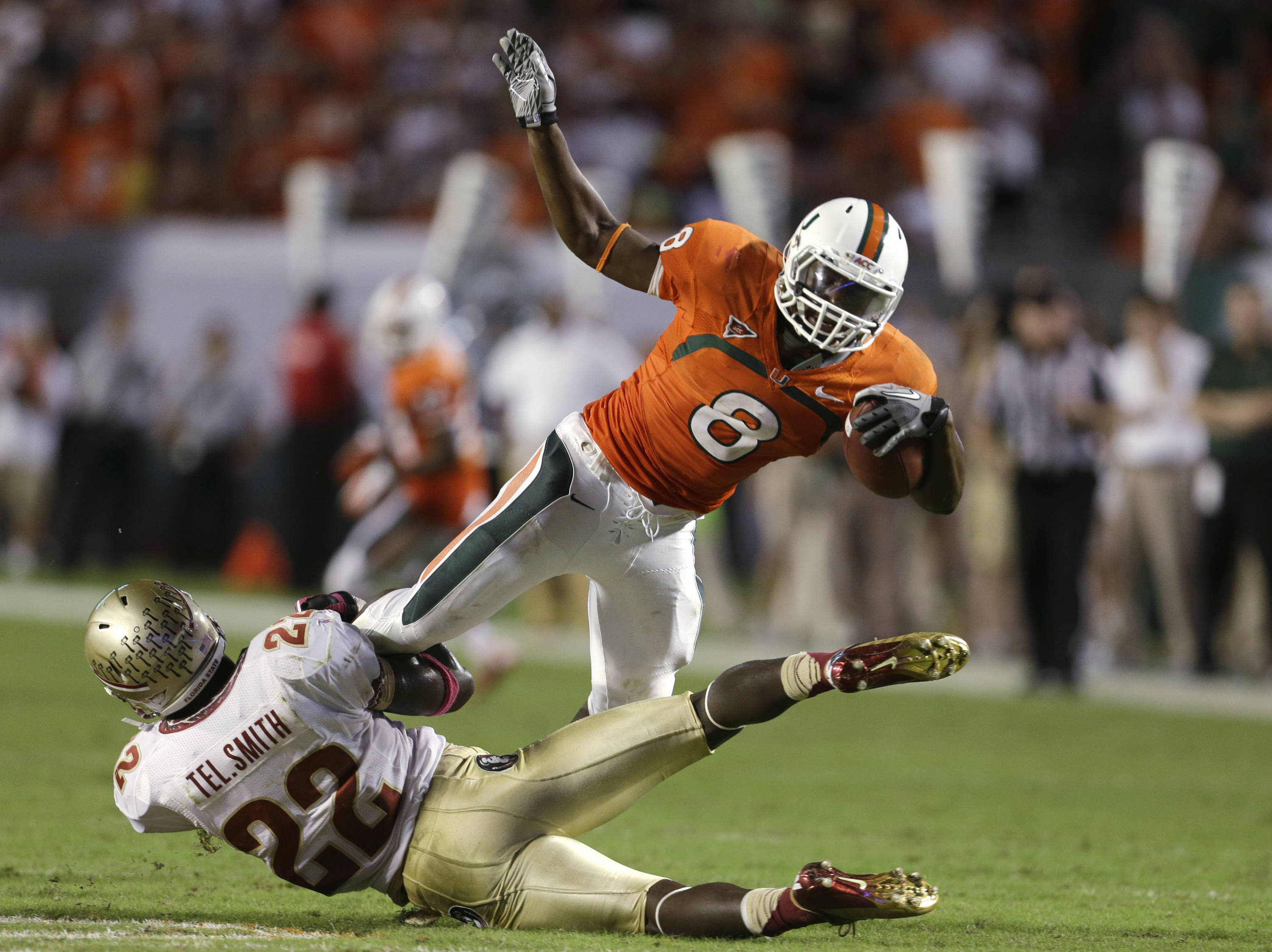 Miami running back Duke Johnson (8) is stopped for a loss by Florida State linebacker Telvin Smith (22) during the first half of an NCAA college football game, Saturday, Oct. 20, 2012, in Miami. (AP Photo/Lynne Sladky)