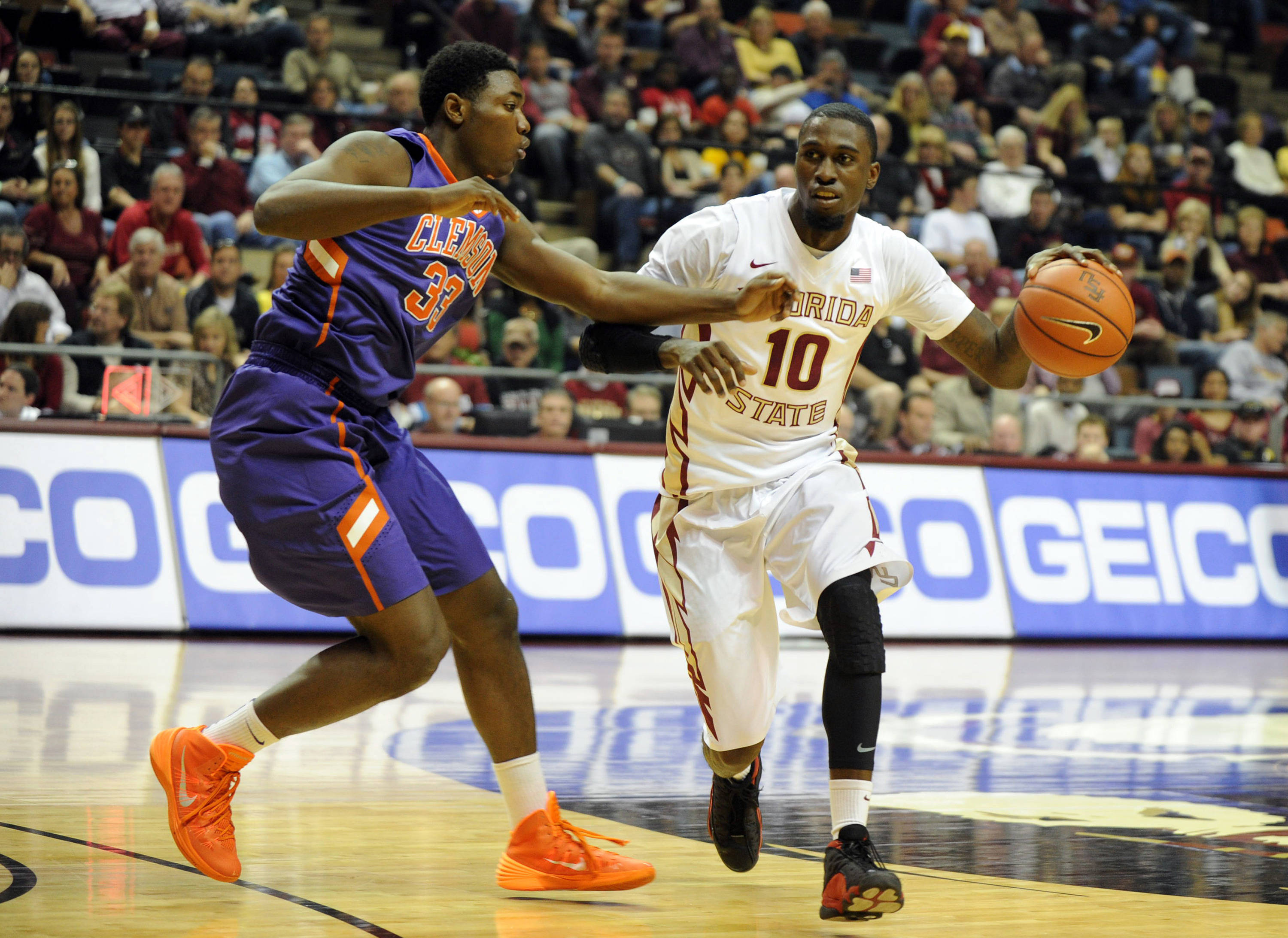 Feb 1, 2014; Tallahassee, FL, USA; Florida State Seminoles forward Okaro White (10) moves the ball past Clemson Tigers forward Josh Smith (33) during the first half at the Donald L. Tucker Center. Mandatory Credit: Melina Vastola-USA TODAY Sports