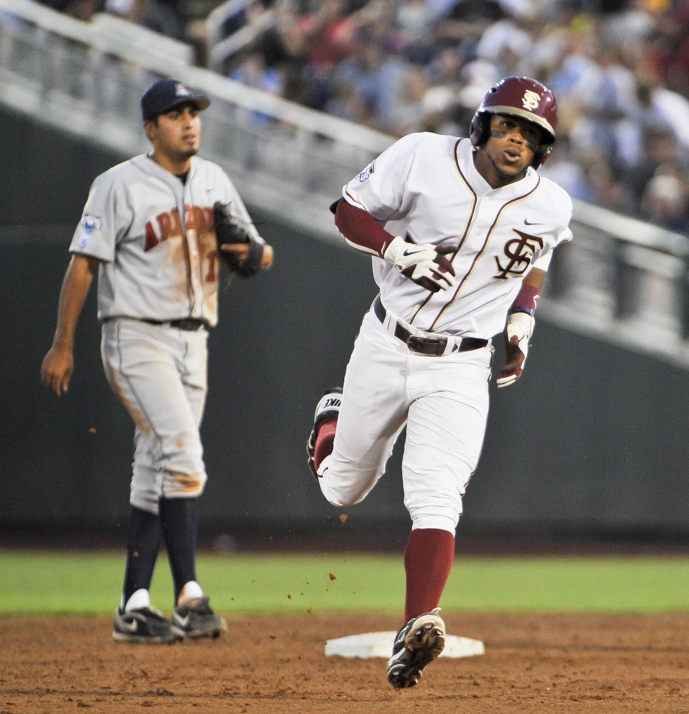 Florida State's Sherman Johnson, right, rounds the bases past Arizona's Alex Mejia, left, after Johnson hit a solo home run in the third inning. (AP Photo/Eric Francis)