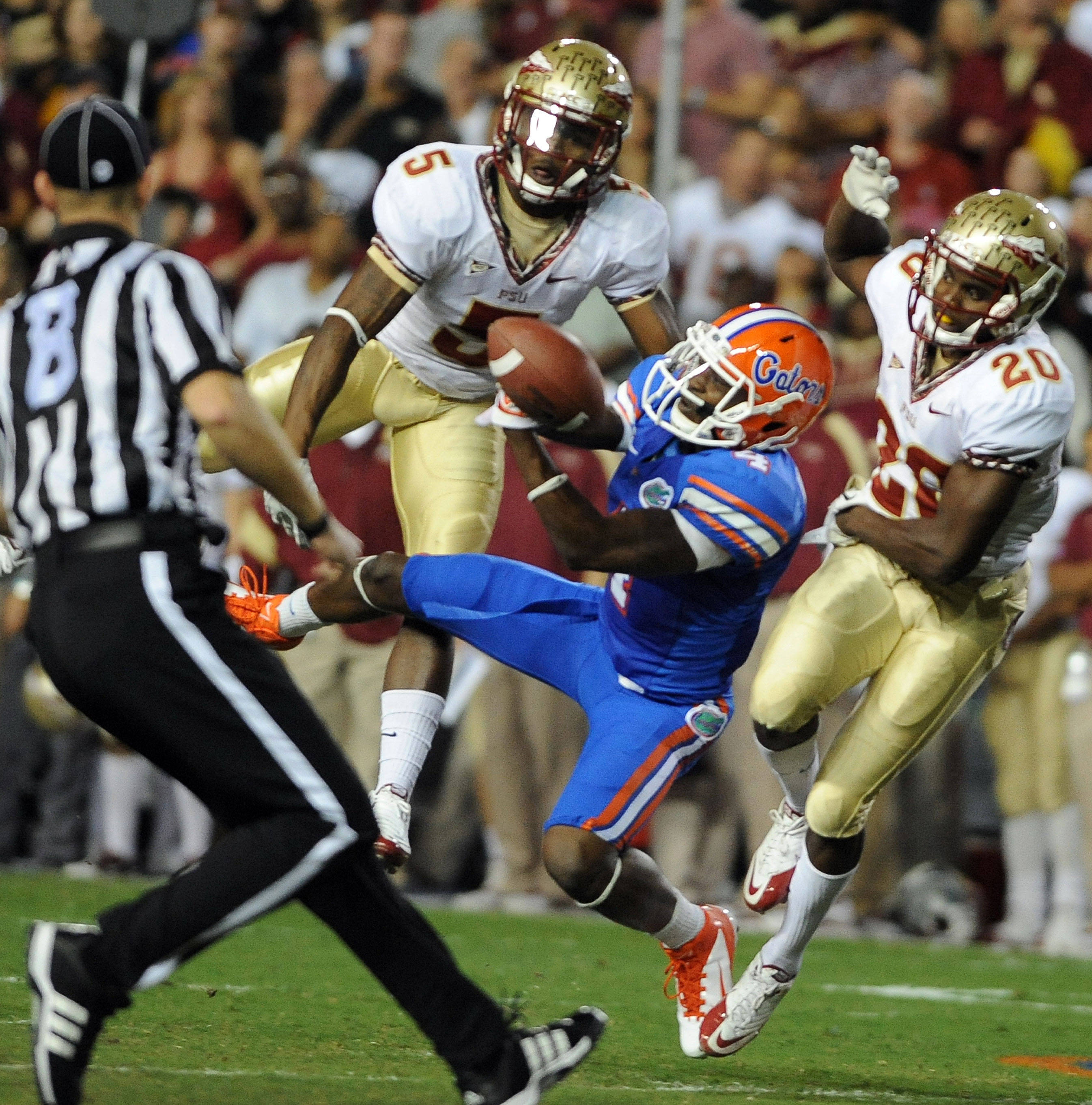 Florida wide receiver Andre Debose (4) tries to hang on to the ball but Florida State's Florida State cornerback Greg Reid (5) and Florida State safety Lamarcus Joyner (20) break up the pass during the first half of an NCAA college football game in Gainesville, Fla.,  Saturday, Nov. 26, 2011. (AP Photo/ Phil Sandlin)