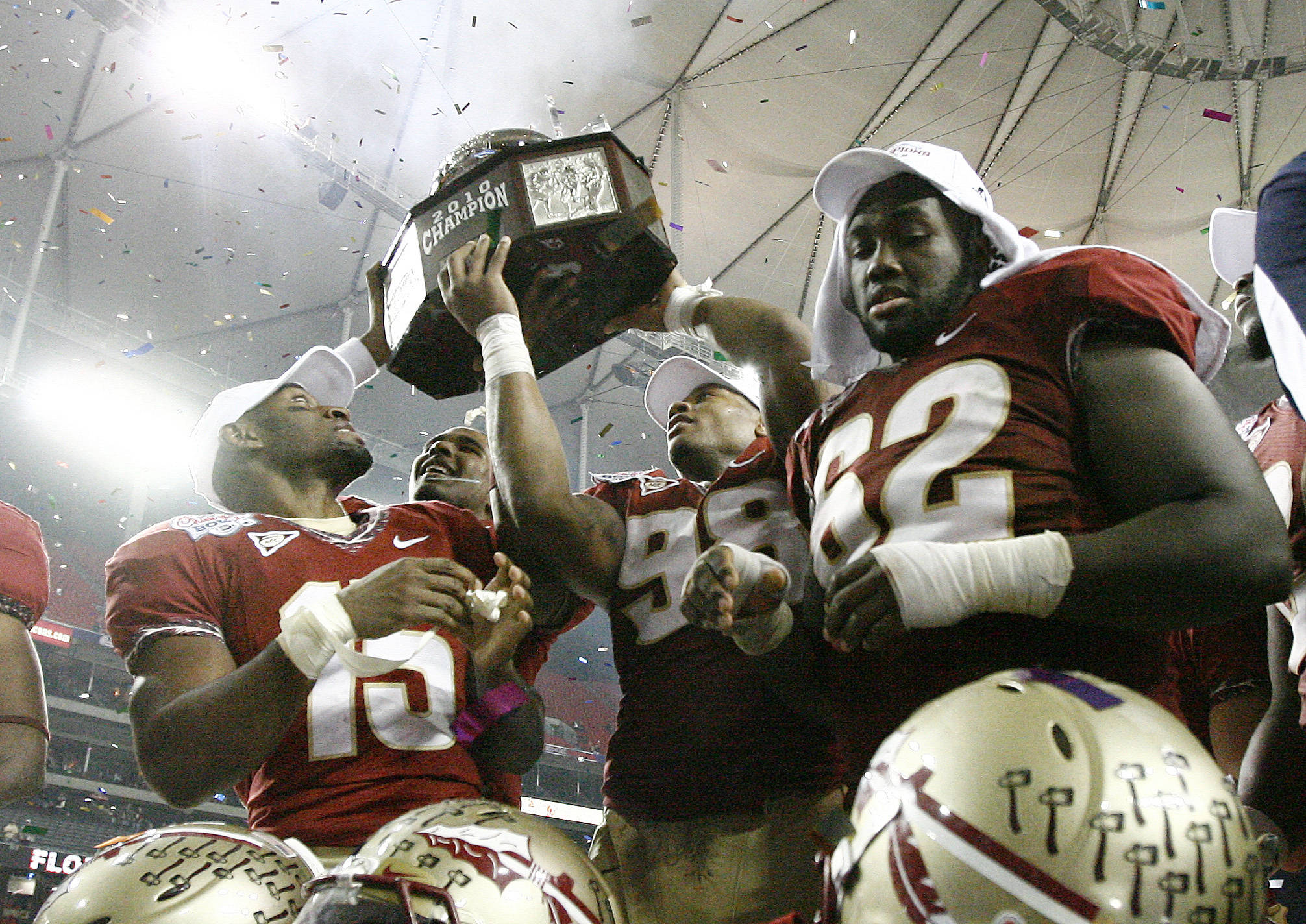 Florida State cornerback Ochuko Jenije (15), defensive end Markus White (98) and guard Rodney Hudson (62) pass the trophy after Florida State defeated South Carolina 26-17 in the Chick-fil-A Bowl on Friday, Dec. 31, 2010, in Atlanta. (AP Photo/John Amis)