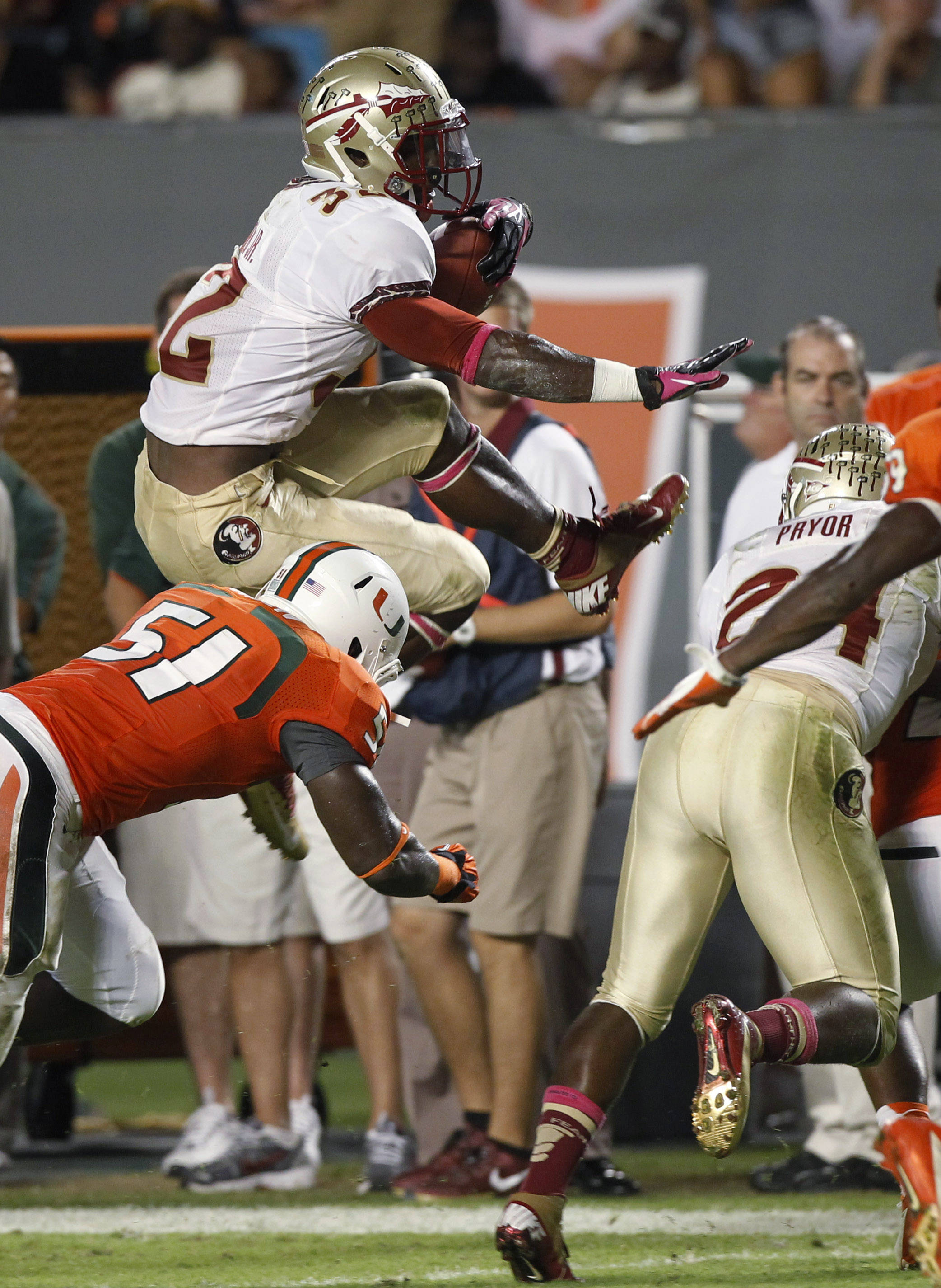 Florida State's James Wilder Jr., top, jumps to avoid Miami's Shayon Green (51)during the first half of an NCAA college football game in Miami, Saturday, Oct. 20, 2012. (AP Photo/Alan Diaz)