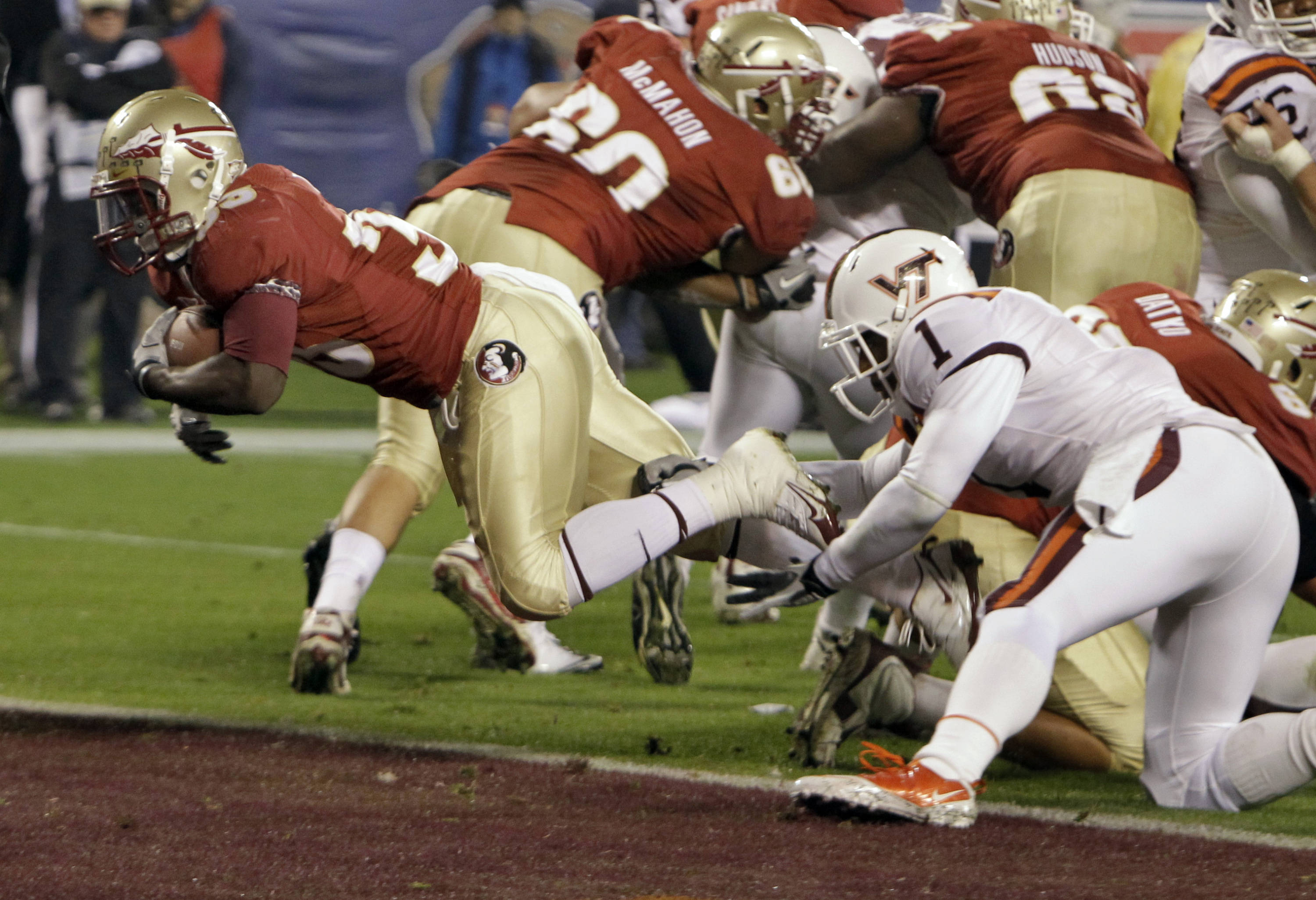 Florida State's Ty Jones dives in for a touchdown as Virginia Tech's Antone Exum reaches in vain.