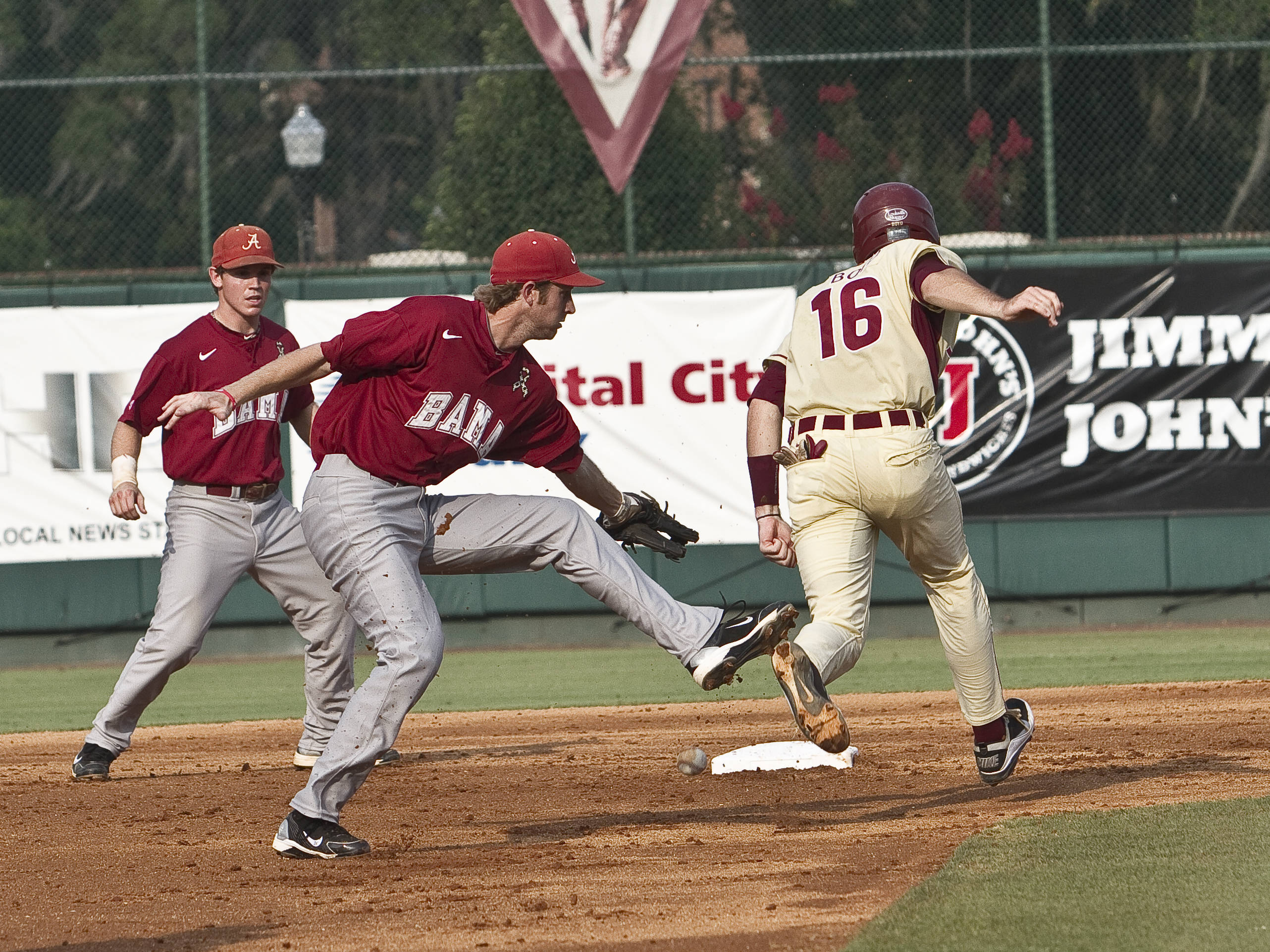 First baseman Jayce Boyd (16) is safe after avoiding the tag in a rundown.