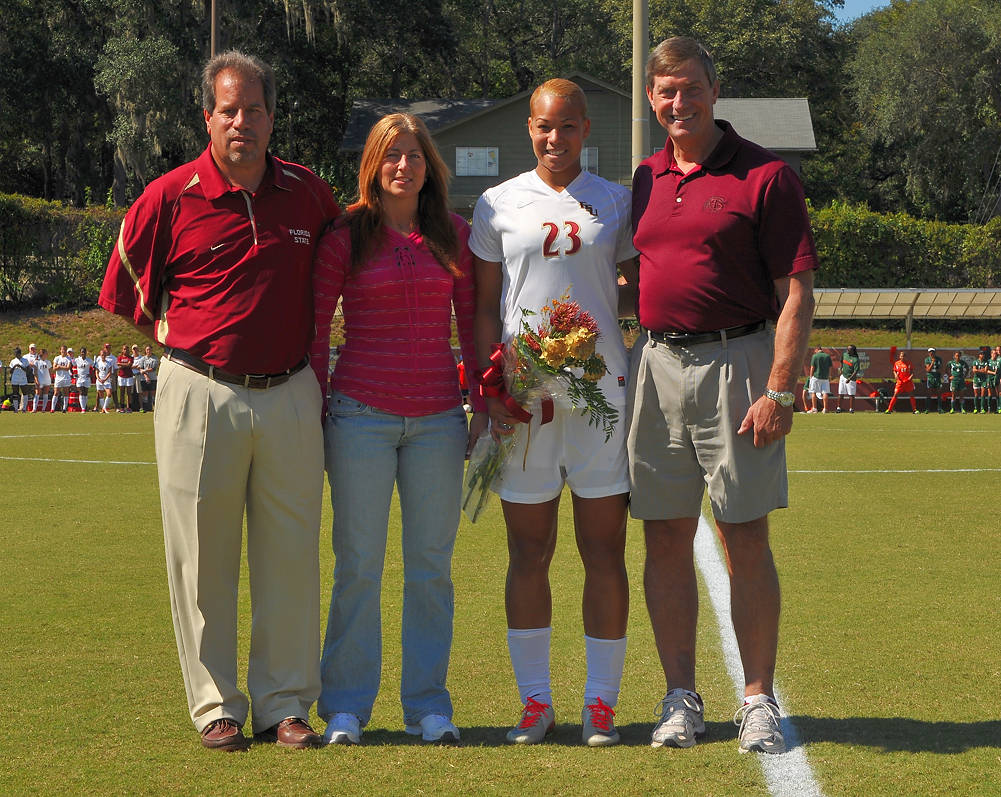 Head coach Mark Krikorian and Director of Athletics Randy Spetman with Toni Pressley and her mom on senior day.