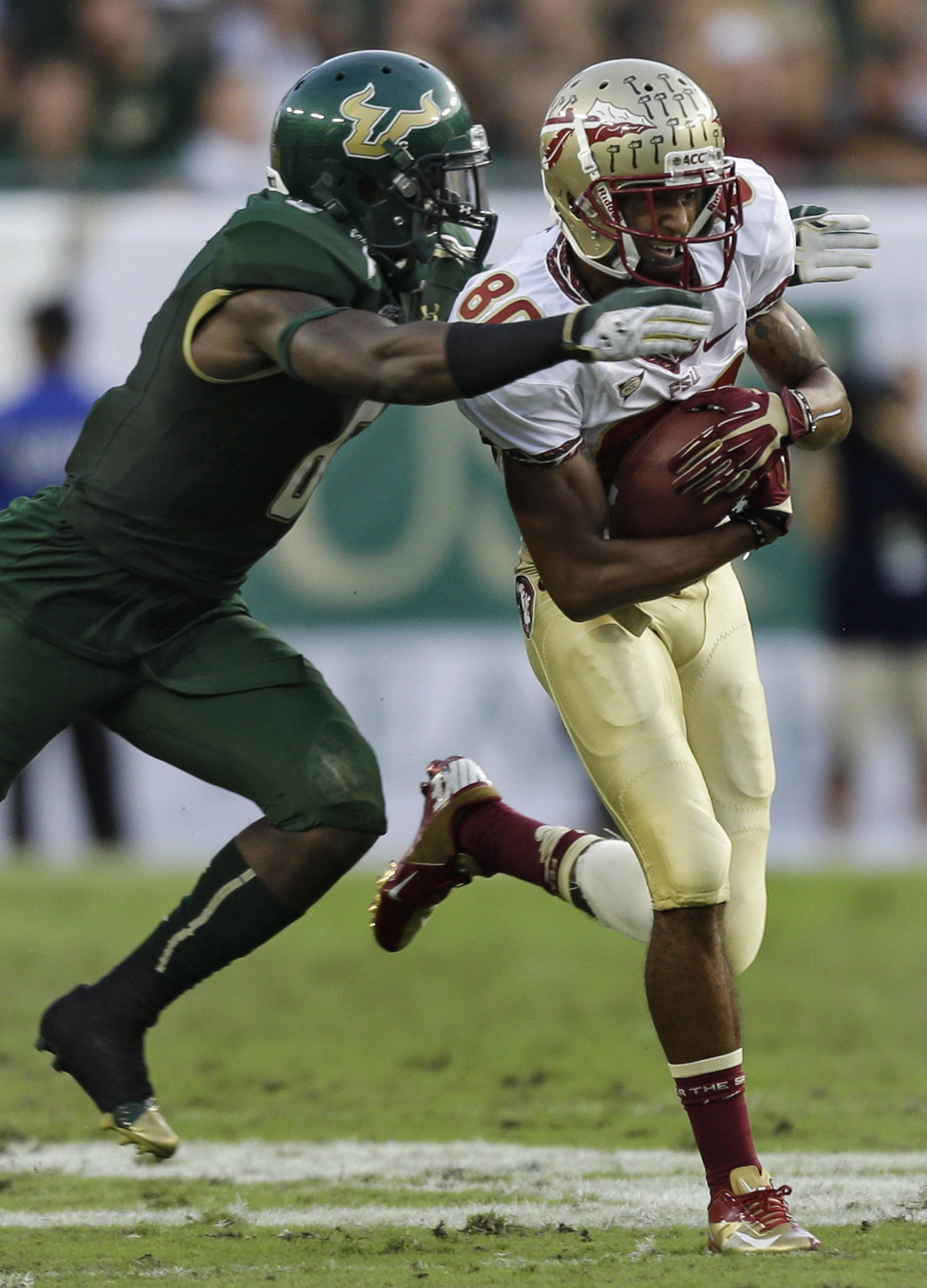Florida State wide receiver Rashad Greene (80) is stopped by South Florida cornerback Kayvon Webster (6) during the second quarter. (AP Photo/Chris O'Meara)