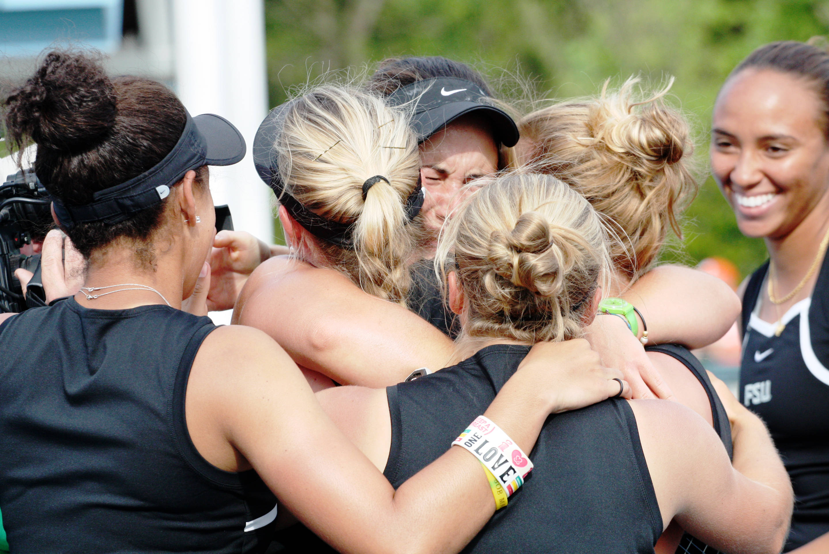 The team hugs Francesca Segarelli after she clinches the match for a berth in the Semifinals of the ACC Championships.