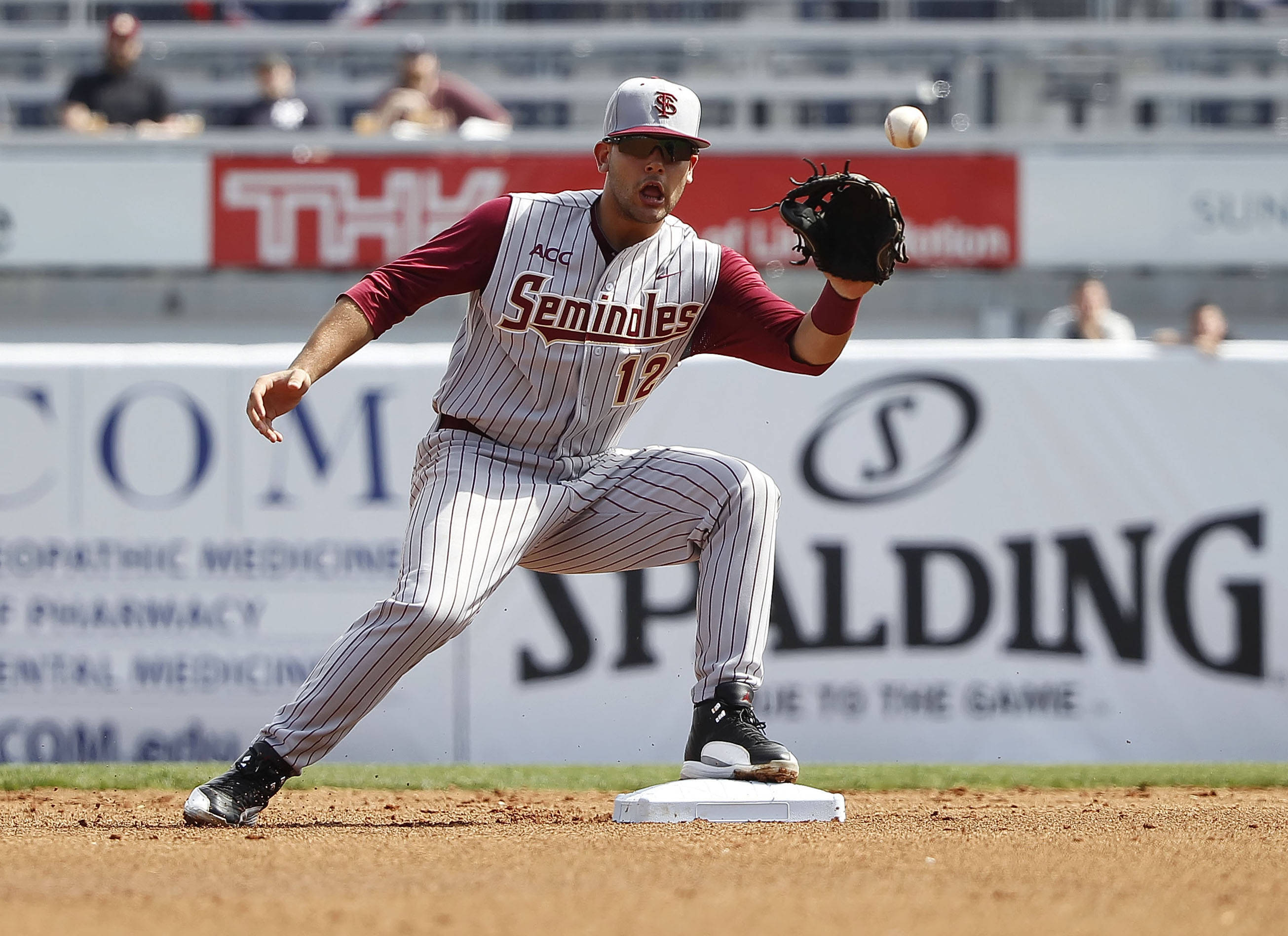 Feb 25, 2014; Tampa, FL, USA;  Florida State Seminoles second baseman John Sansone (12) catches the ball and throws it to first base for a double play during the first inning at George M. Steinbrenner Field. Mandatory Credit: Kim Klement-USA TODAY Sports
