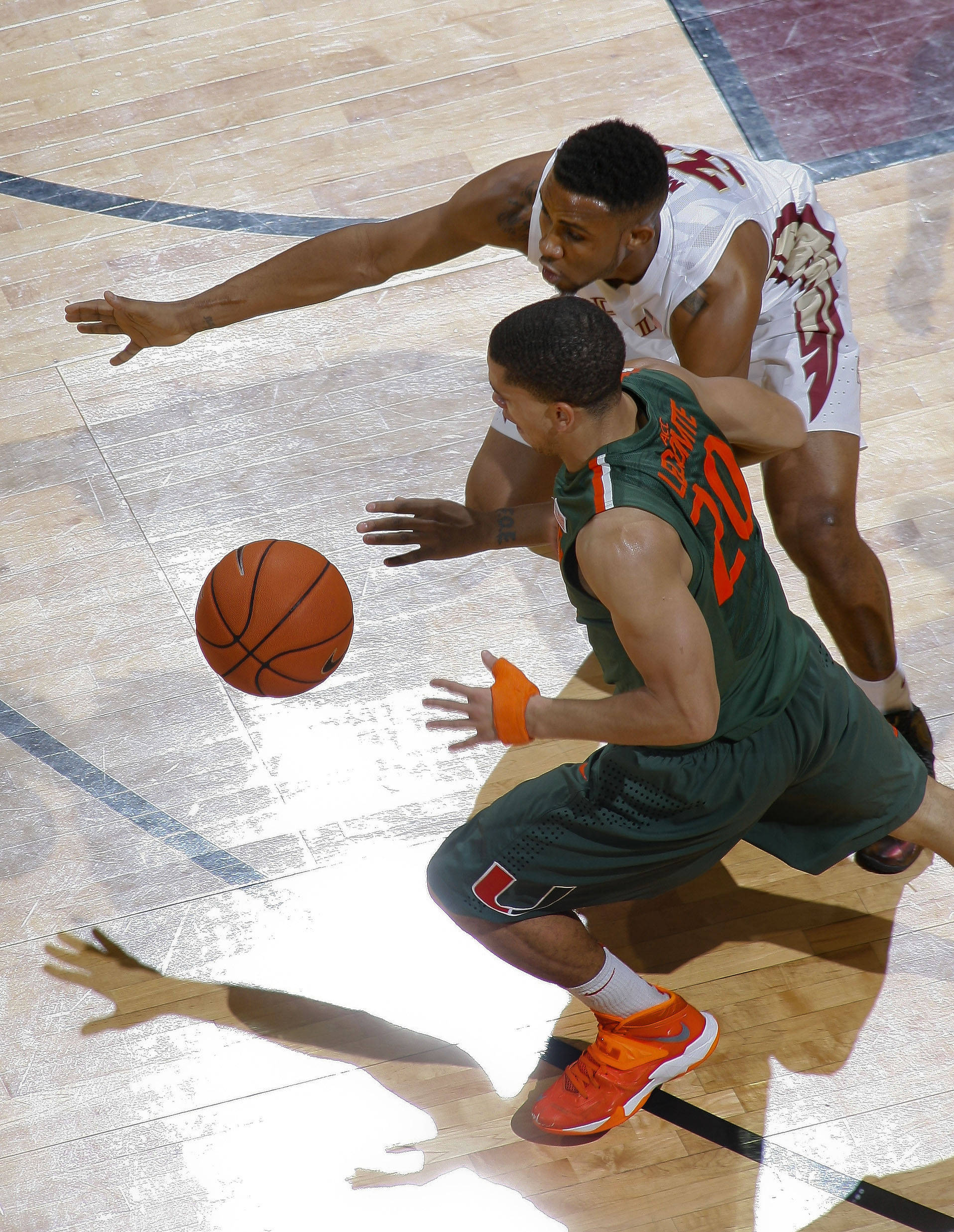 Feb 10, 2014; Tallahassee, FL, USA; Seminoles guard Ian Miller (30) and Miami Hurricanes guard Manu Lecomte (20) chase a loose ball in the first half. Phil Sears-USA TODAY Sports