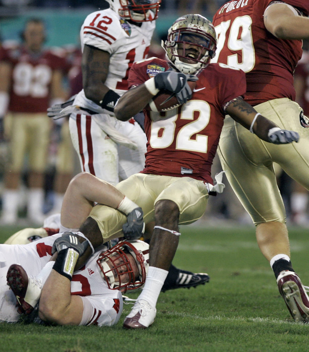 Florida State receiver Taiwan Easterling (82) is stopped by Wisconsin defensive lineman Jeff Stehle, lower left, after a short gain during the first half. (AP Photo/John Raoux)