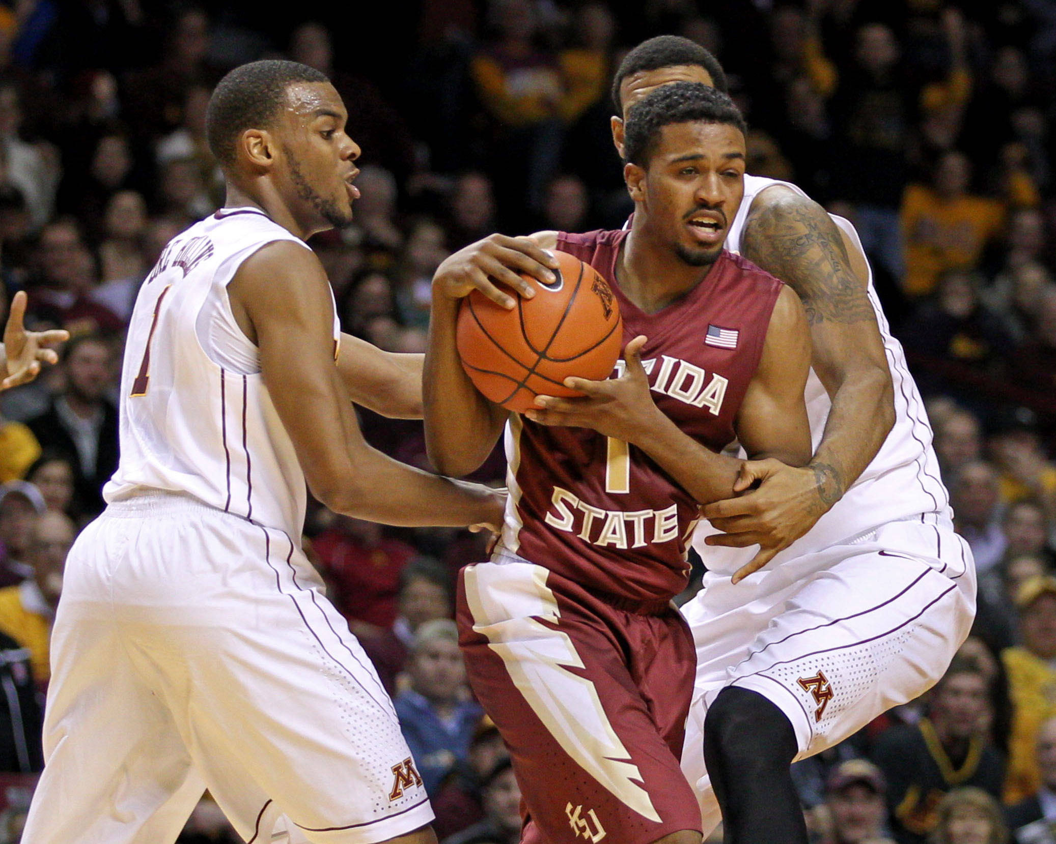 Dec 3, 2013; Minneapolis, MN, USA; Florida State Seminoles guard Devon Bookert (1) guarded by Minnesota Golden Gophers guard Andre Hollins (1) and forward Maurice Walker (15) during the first half at Williams Arena. Mandatory Credit: Brace Hemmelgarn-USA TODAY Sports