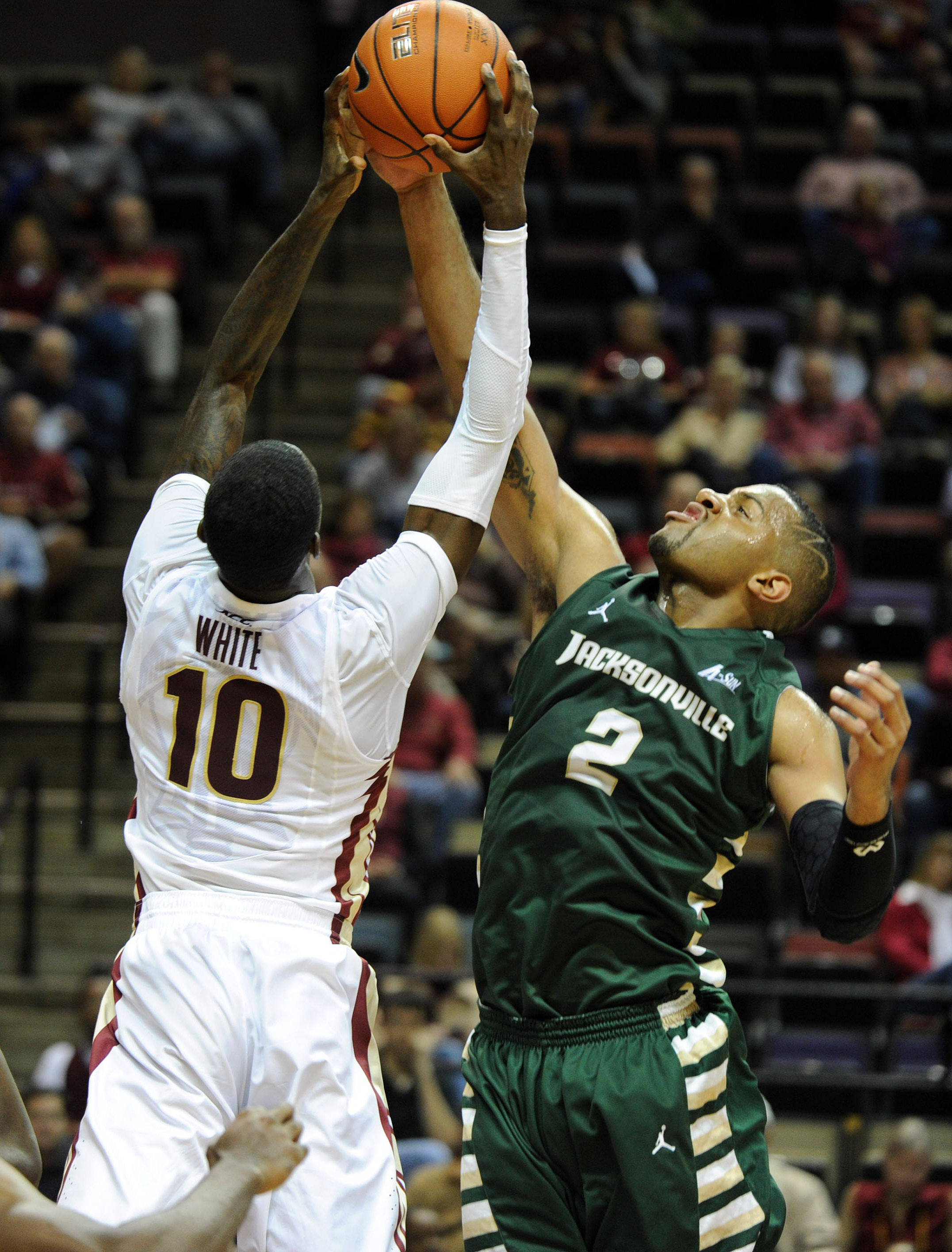Nov 8, 2013; Tallahassee, FL, USA; Jacksonville Dolphins forward Kordario Fleming (2) tries to recover a rebound past Florida State Seminoles forward Okaro White (10) during the first half at the Donald L. Tucker Center. Mandatory Credit: Melina Vastola-USA TODAY Sports
